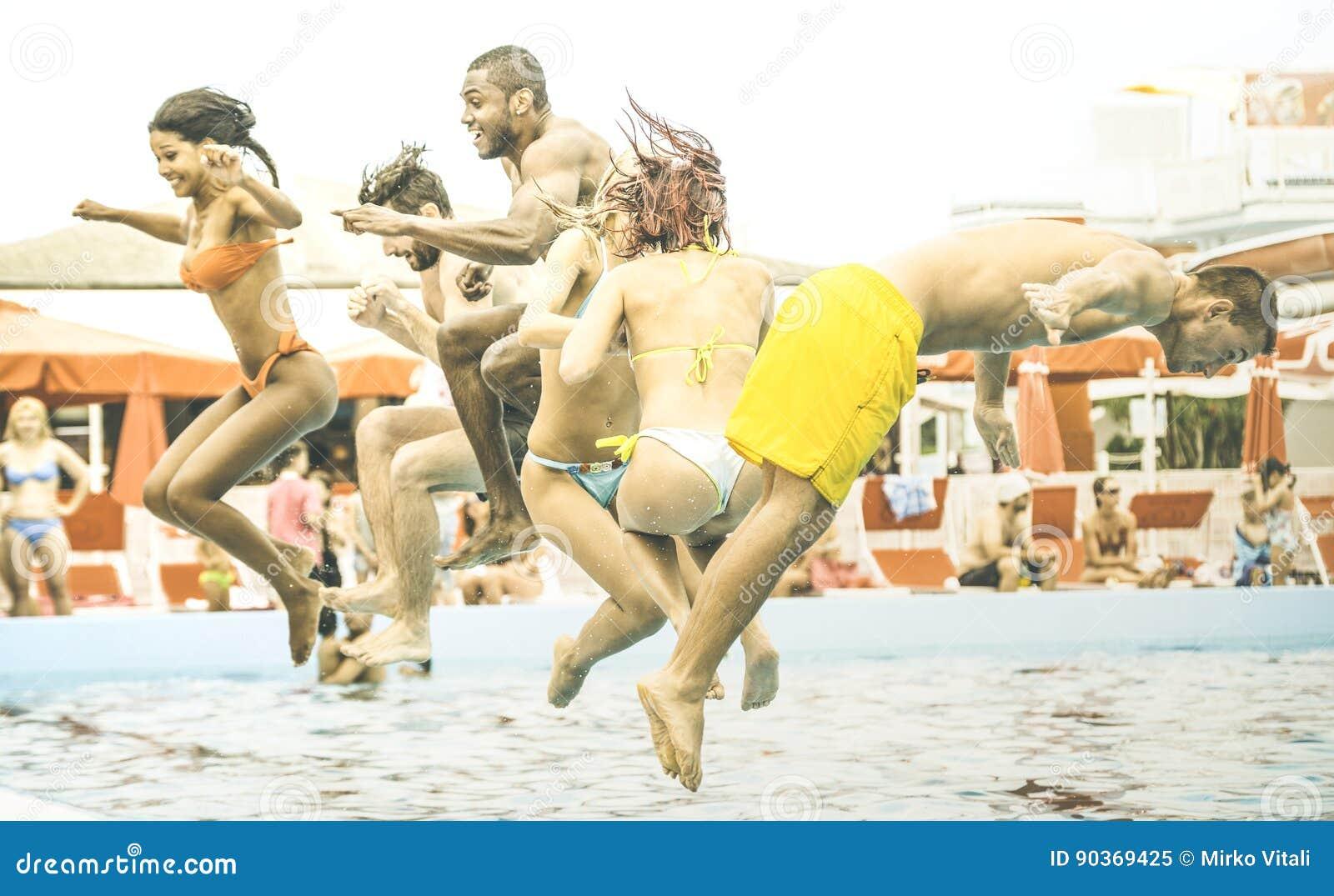 Blandras- vänner som har rolig banhoppning på aquapark för simbassängparti