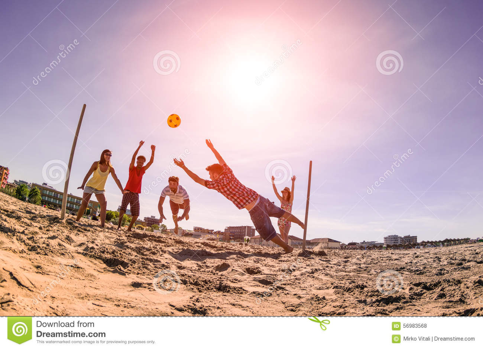 Blandras- vänner som spelar fotboll på stranden - begrepp av mång- c
