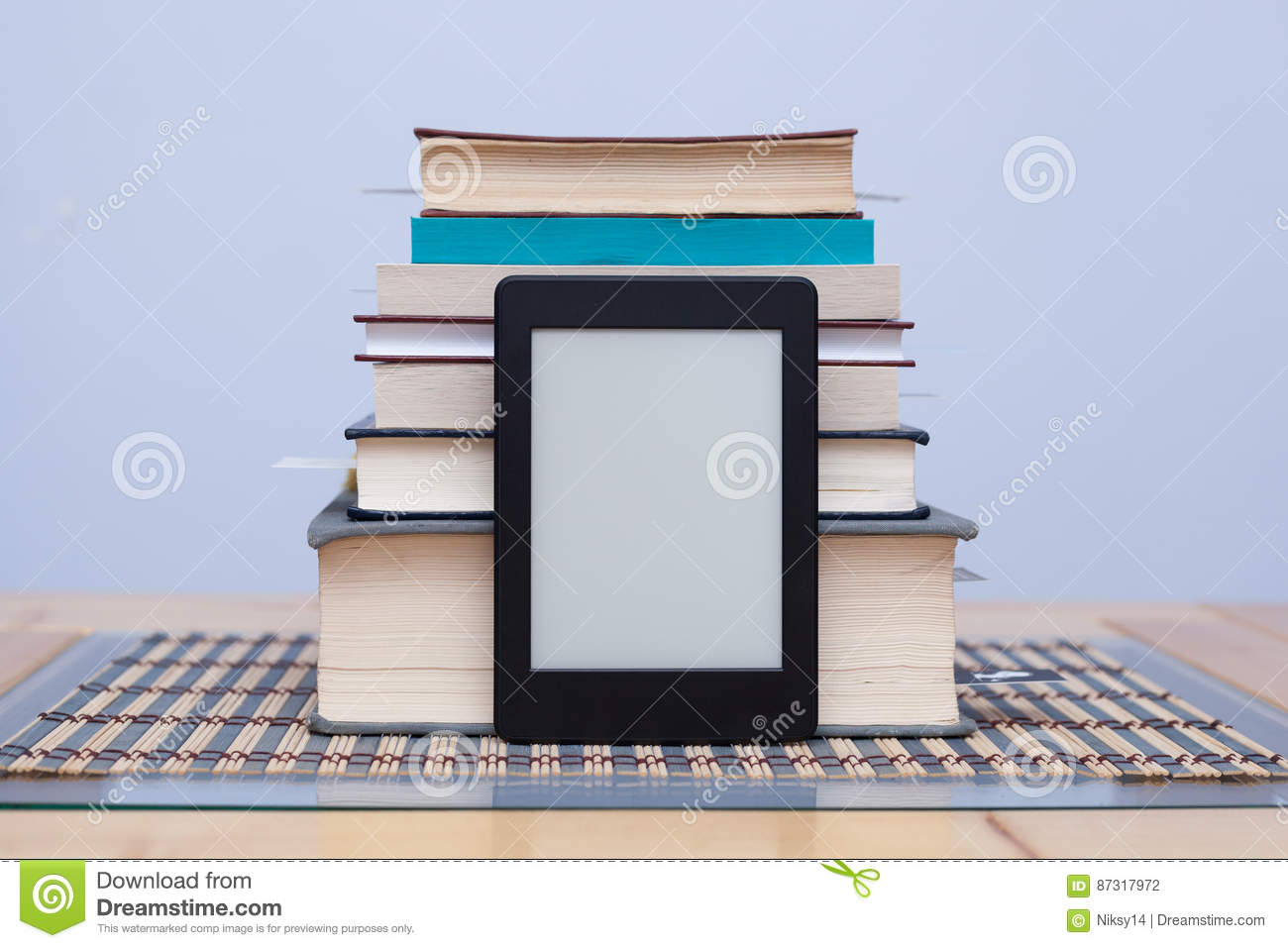 Blank eReader in front of a tower of books with bookmarks