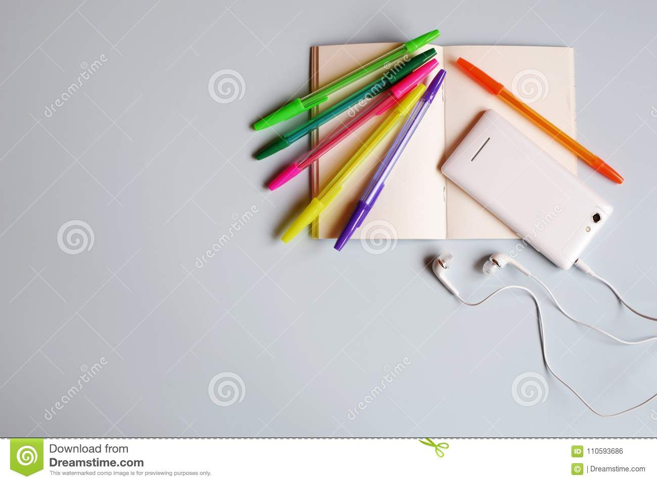 Blank notebook or diary, smart phone with earphones and multicolored pens