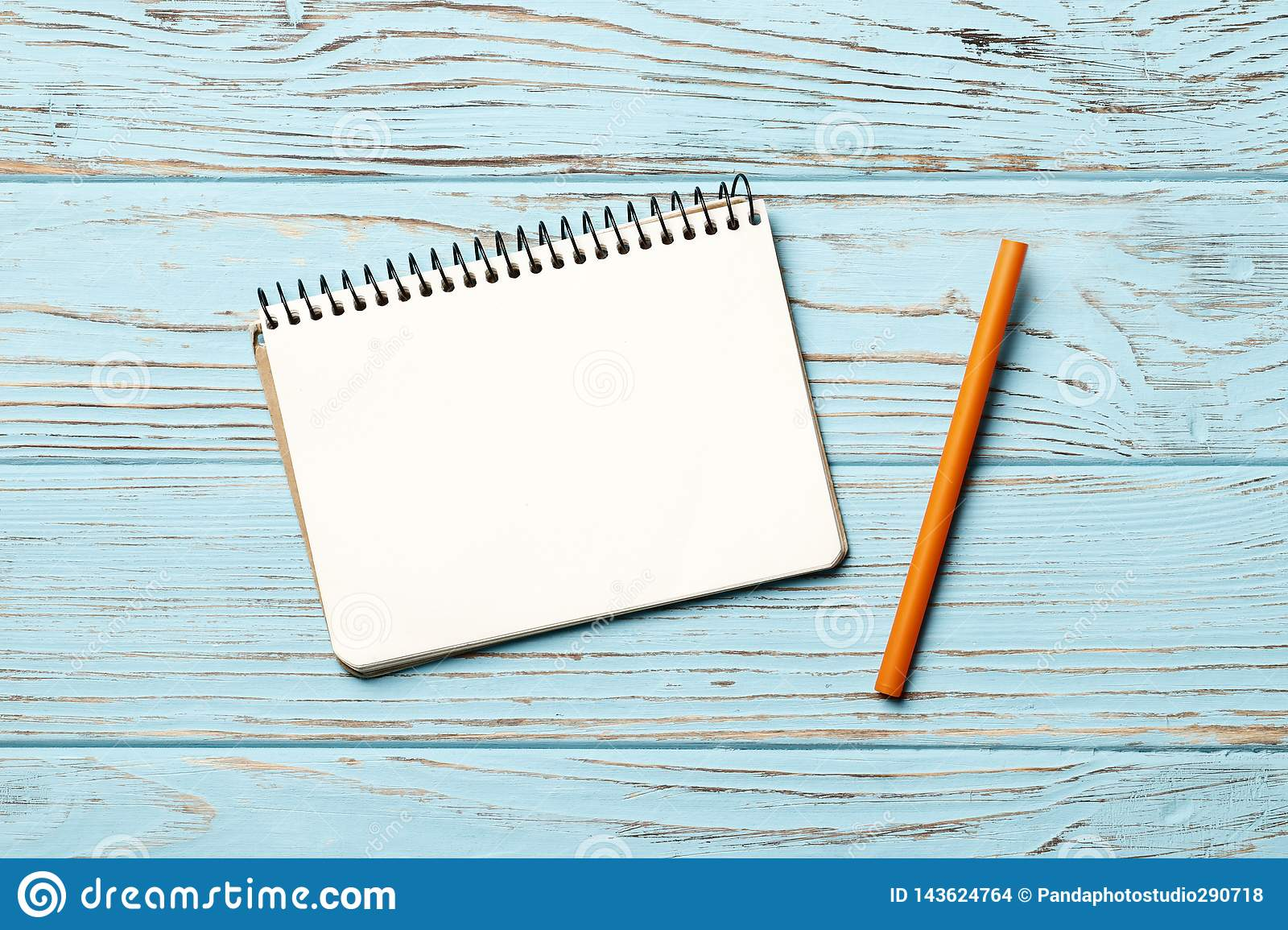 paper notebook with pen on blue wooden background