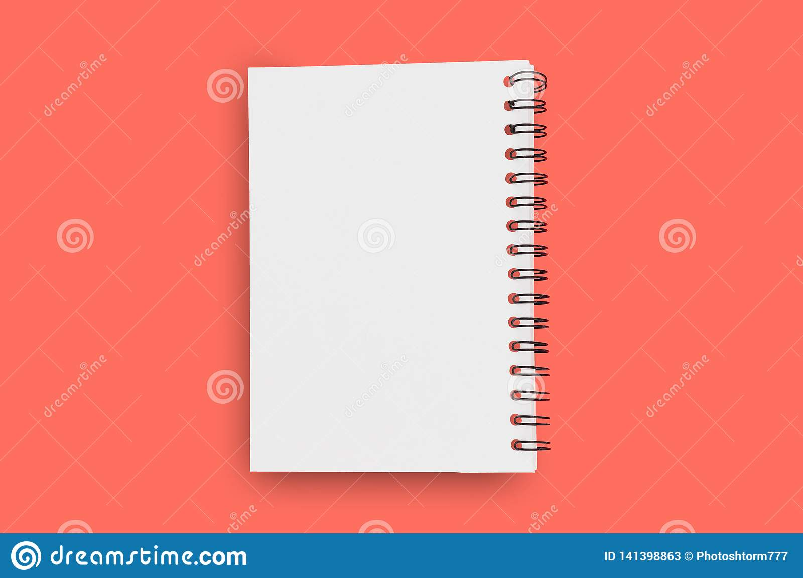 Blank paper notepad with spiral wire for note or drawing in center on background of living coral color. Copy space for your text