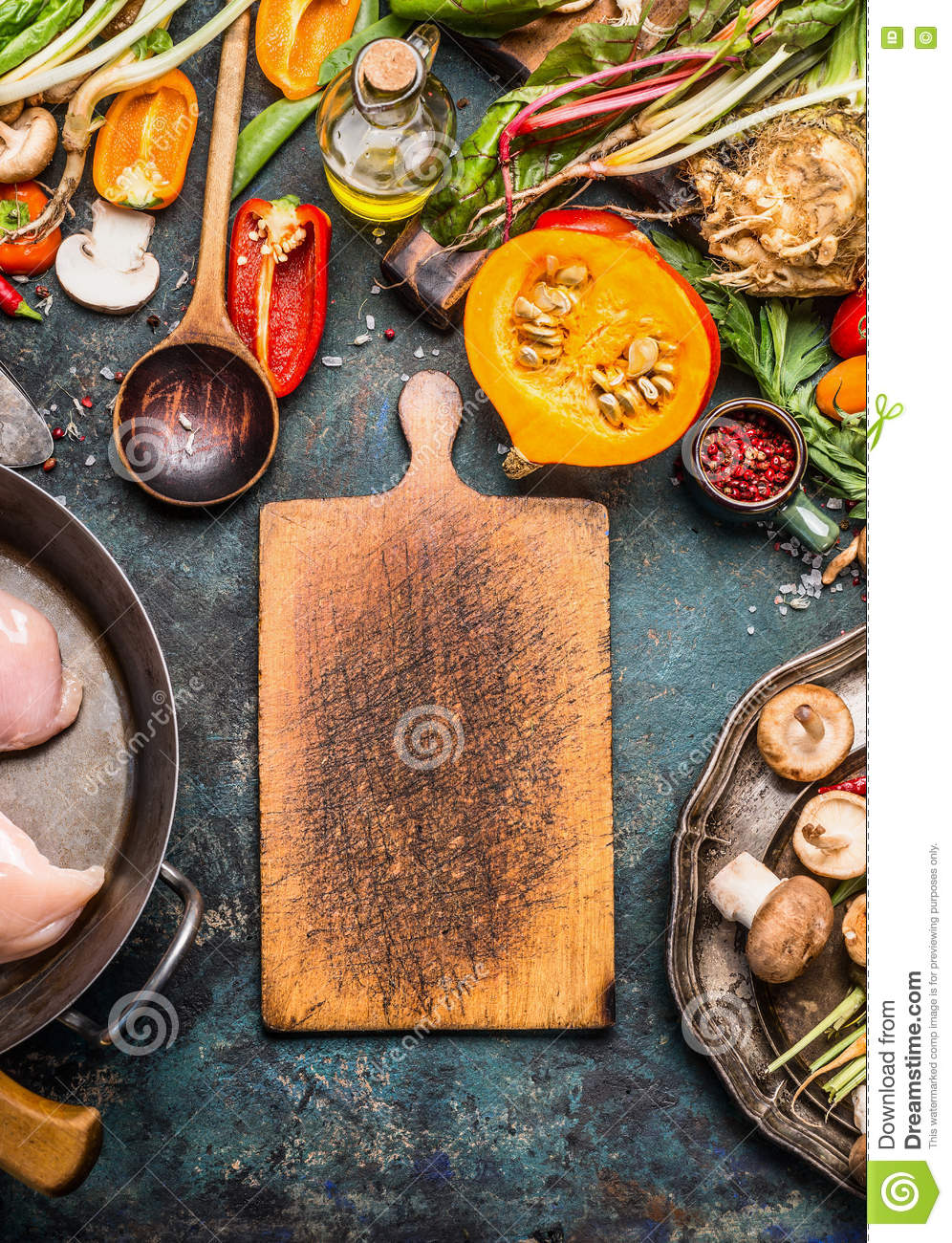 Blank rustic cutting board and Pumpkin with organic vegetables ingredients for tasty cooking on dark kitchen table
