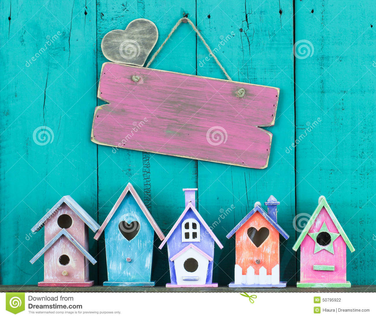Blank sign with heart hanging by row of birdhouses