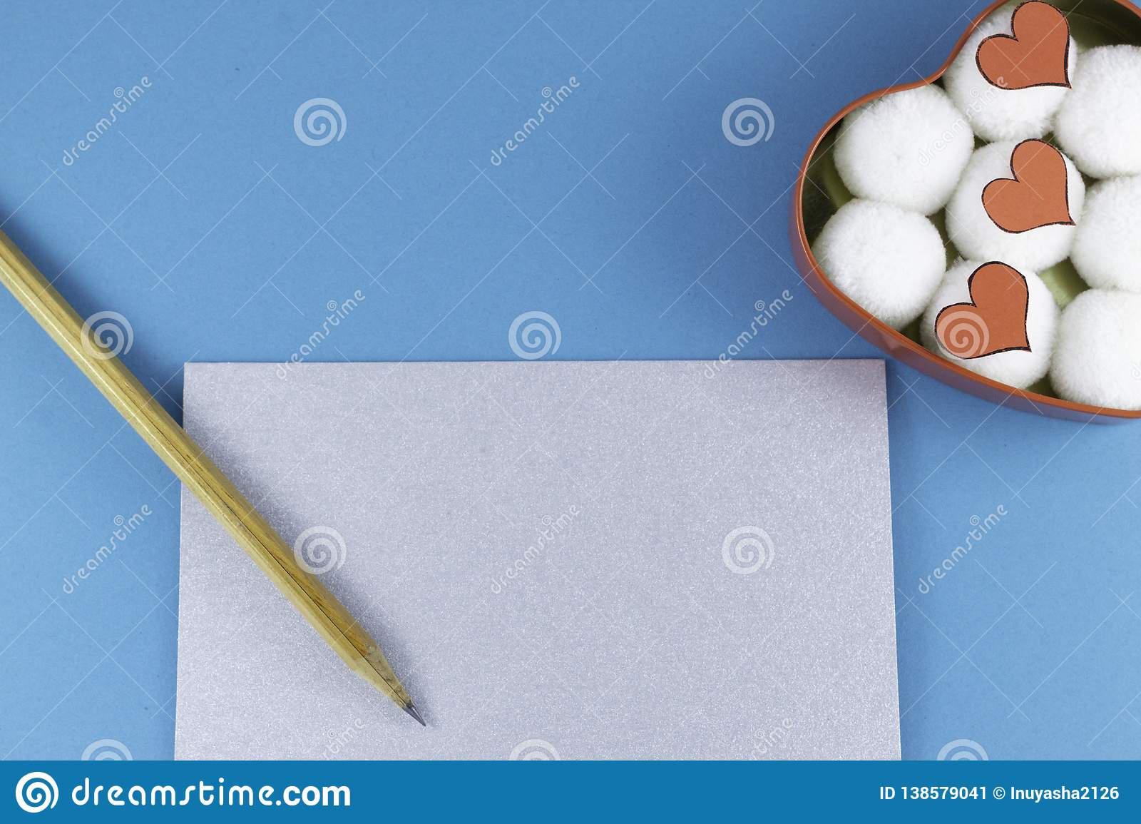 A blank silver letter with a wooden pencil and a heart-shaped box with cotton balls and hearts inside on a blue background