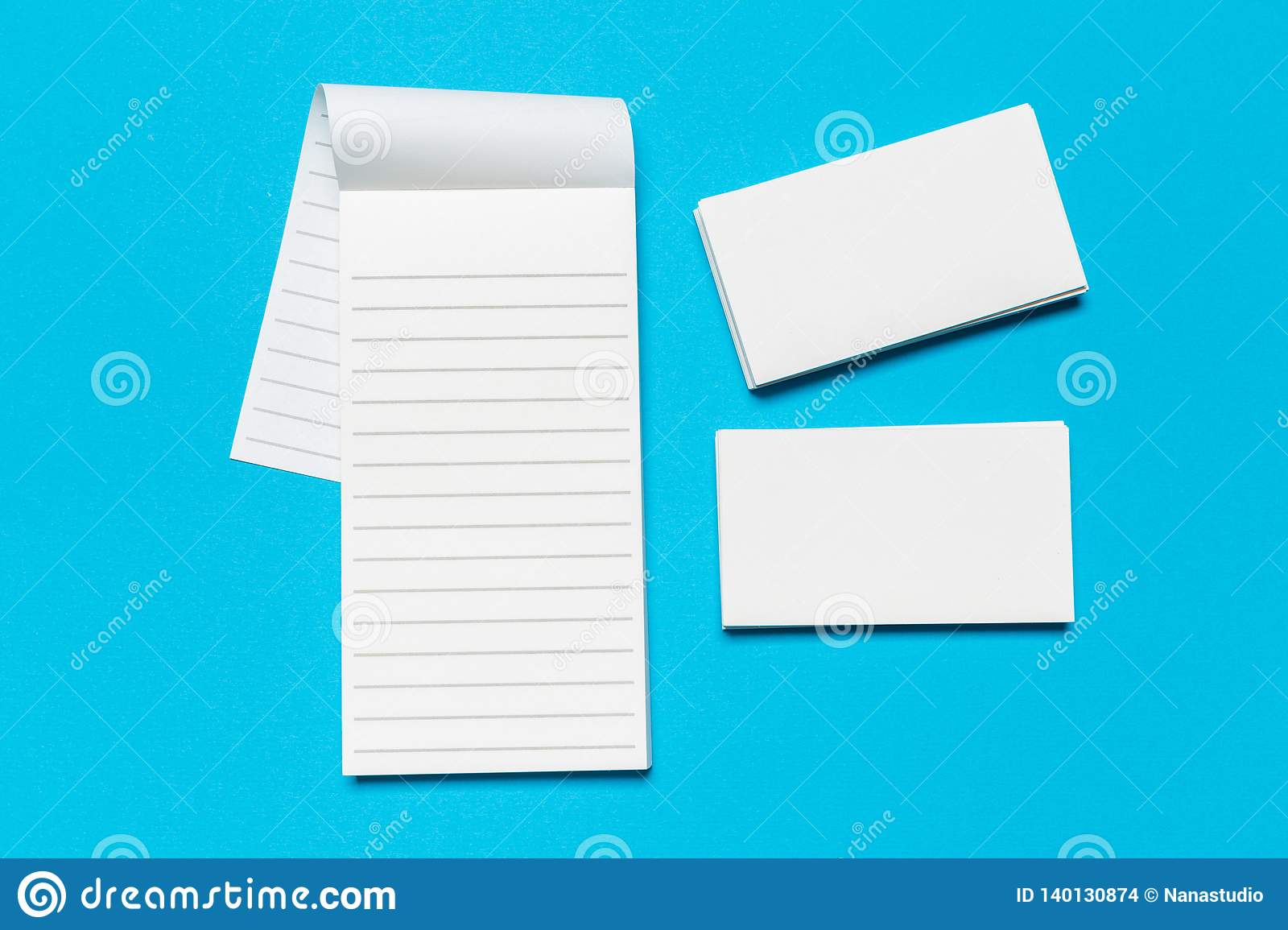 Blank white business cards on blue background. Mockup for branding identity