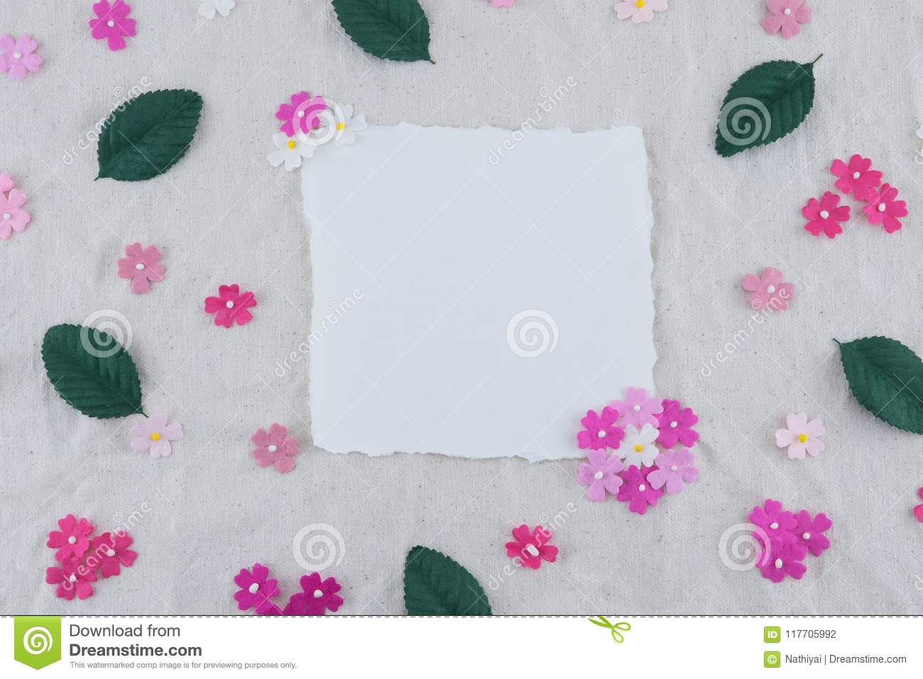1000d379f35 Blank white card decorated with pink tone paper flowers and green leaves on  muslin fabric