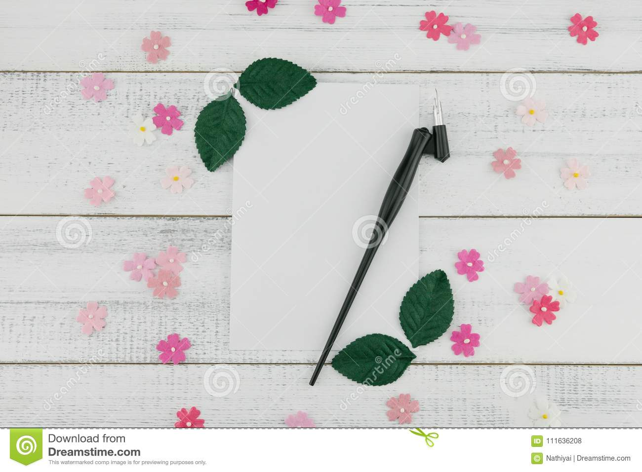 055d201e9f4 Blank white card and oblique pen decorate with pink paper flowers and green  leaves on white wood background