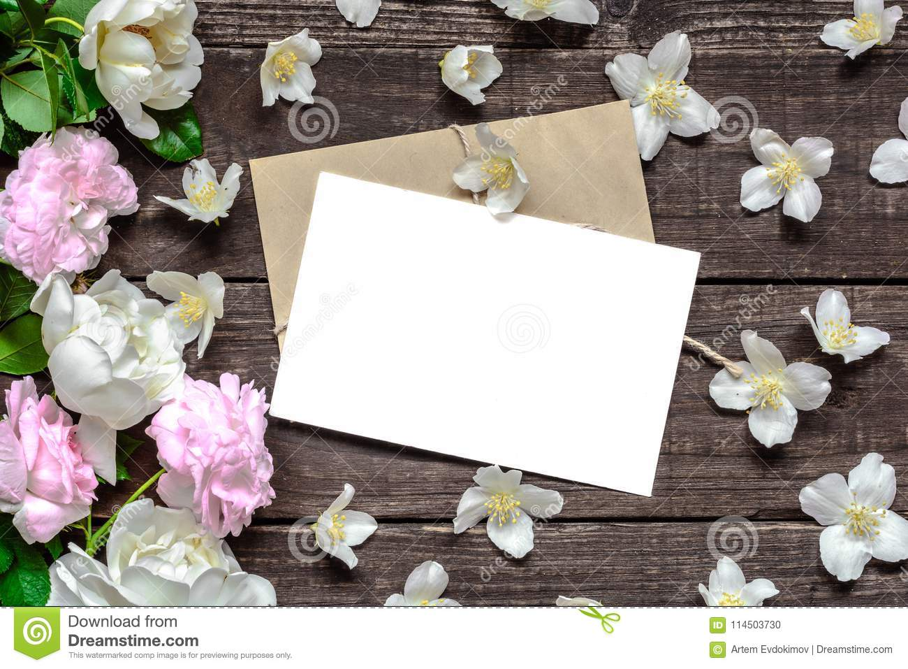 Blank white greeting card in frame made of pink roses and white jasmine flowers and envelope on rustic wooden background