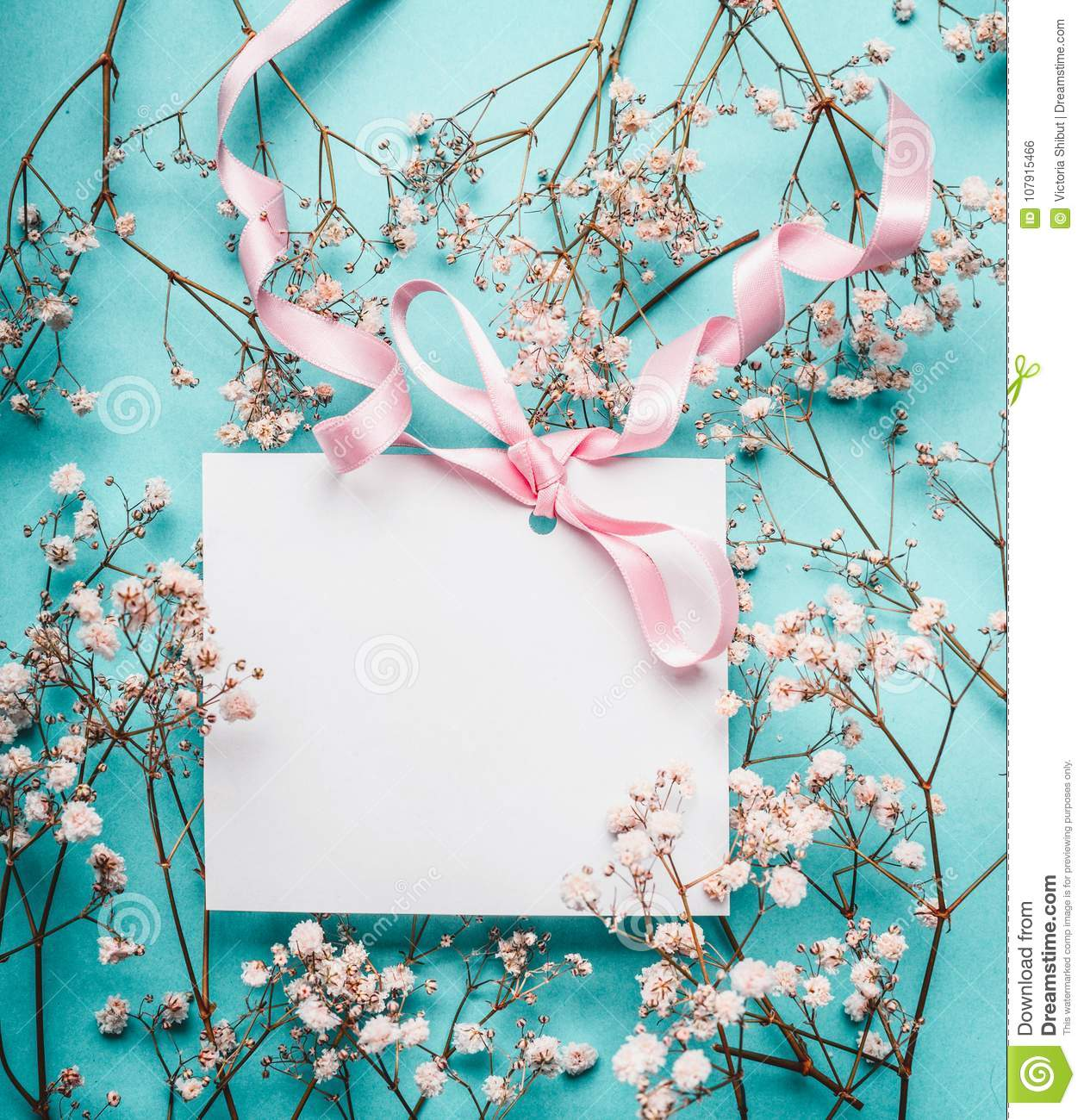Blank white greeting card with pink ribbon on little white flowers at turquoise blue background