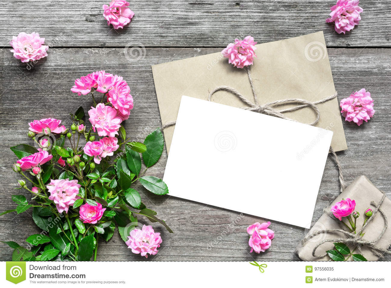 Blank white greeting card with pink rose flowers bouquet and envelope with flower buds and gift box