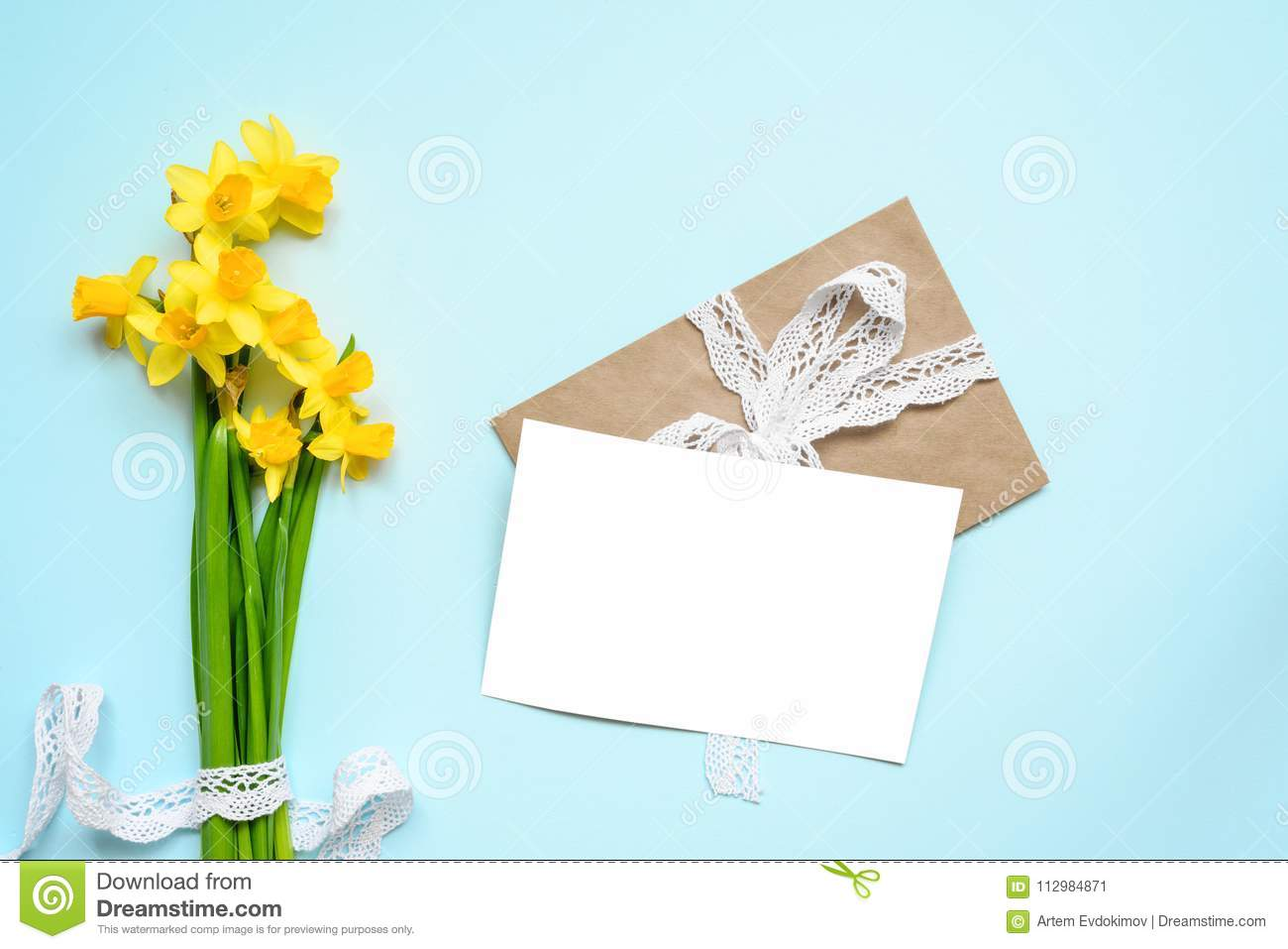 Blank white greeting card with spring yellow narcissus flowers bouquet over blue background. mock up
