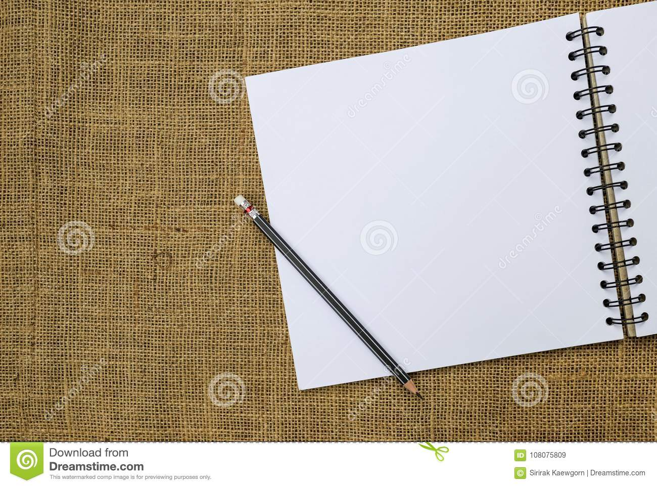 Blank white sketch book and black pencil with space on hessian fabric background