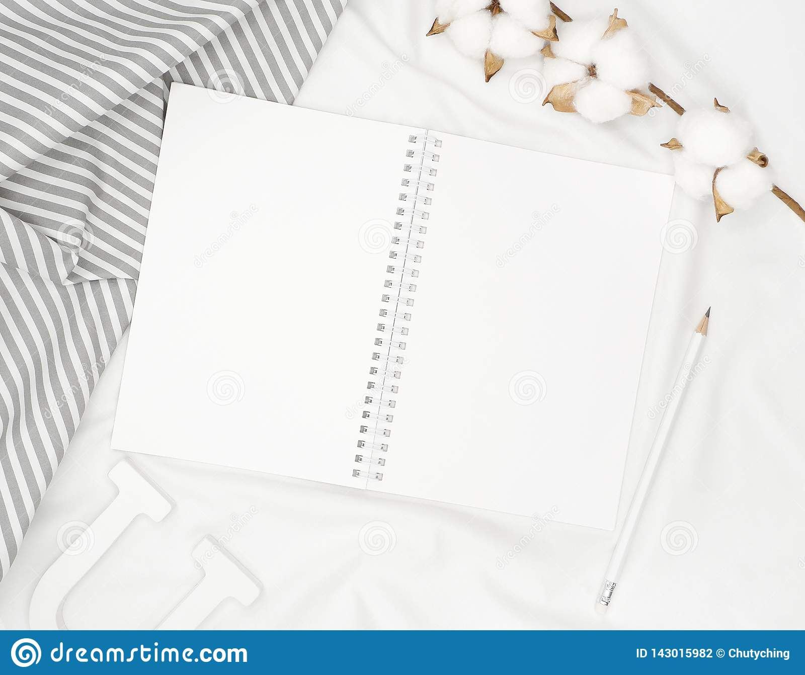 Blank white spiral notebook with pencil, cotton flowers, grey stripe fabric and wooden letter on white bed sheet.