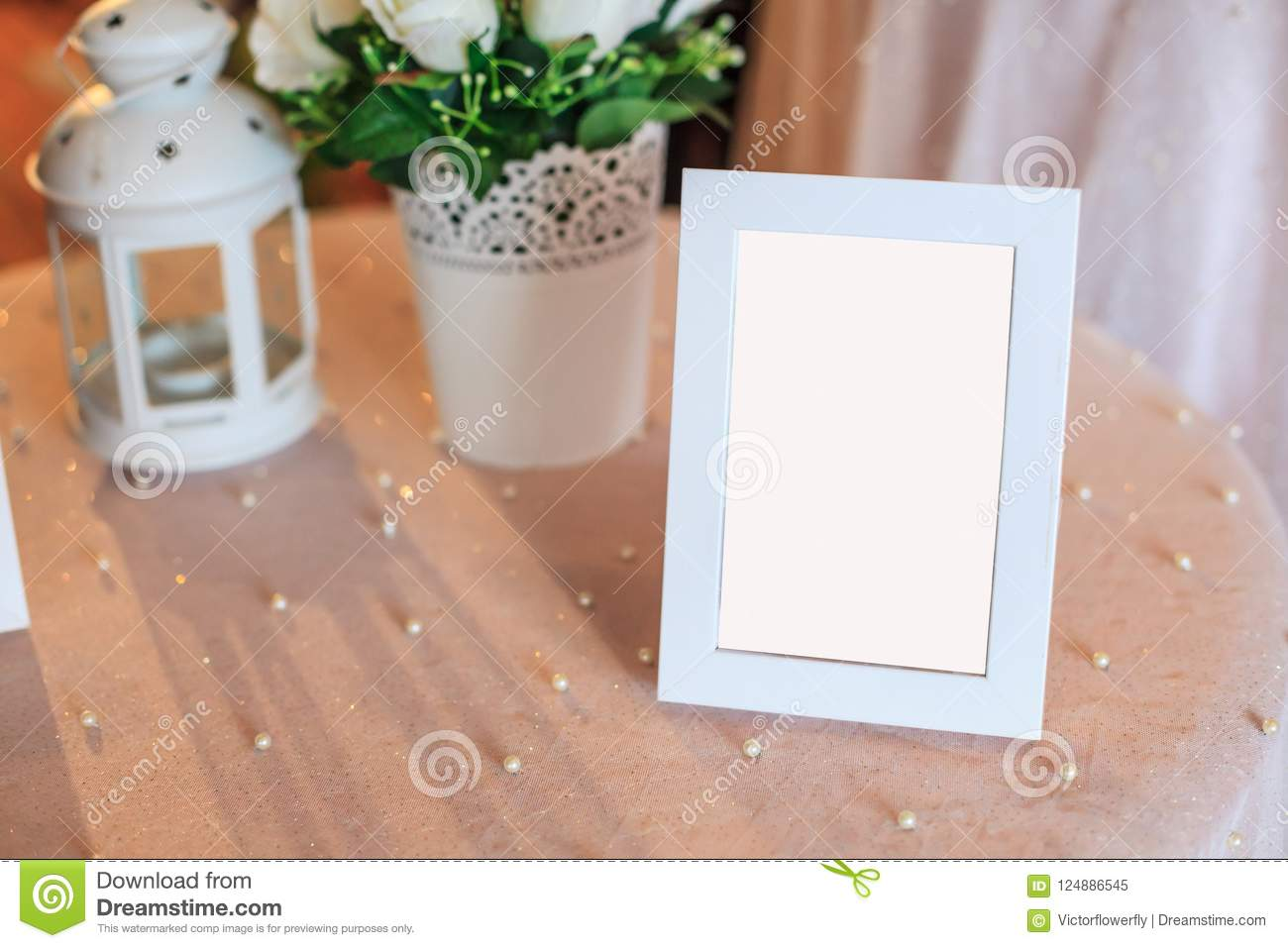 Blank wooden picture frame decoration on table decorated by white tablecloth. Wedding reception ceremony, anniversary celebration