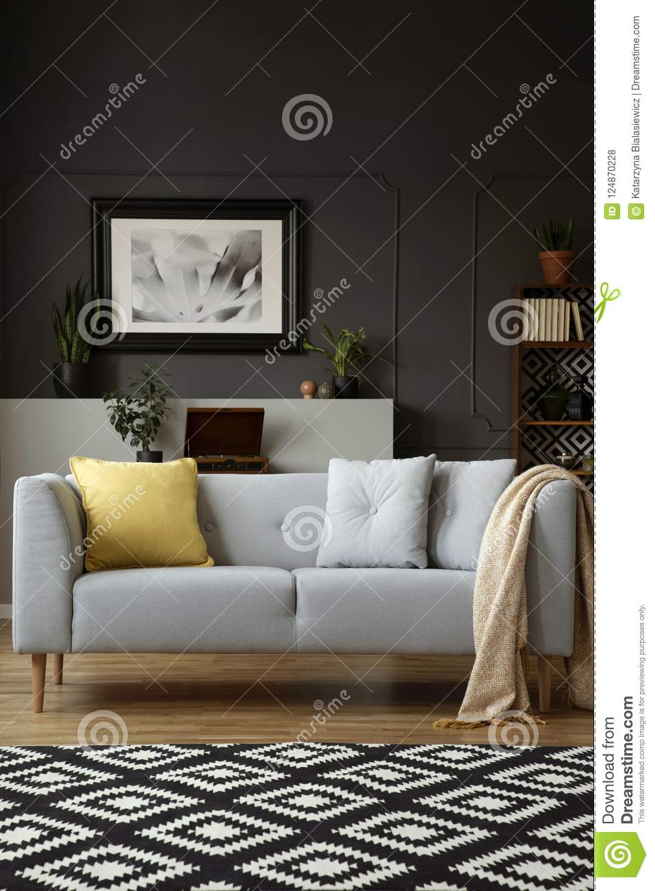Blanket on grey settee with yellow cushion in living room interior with carpet and poster. Real photo