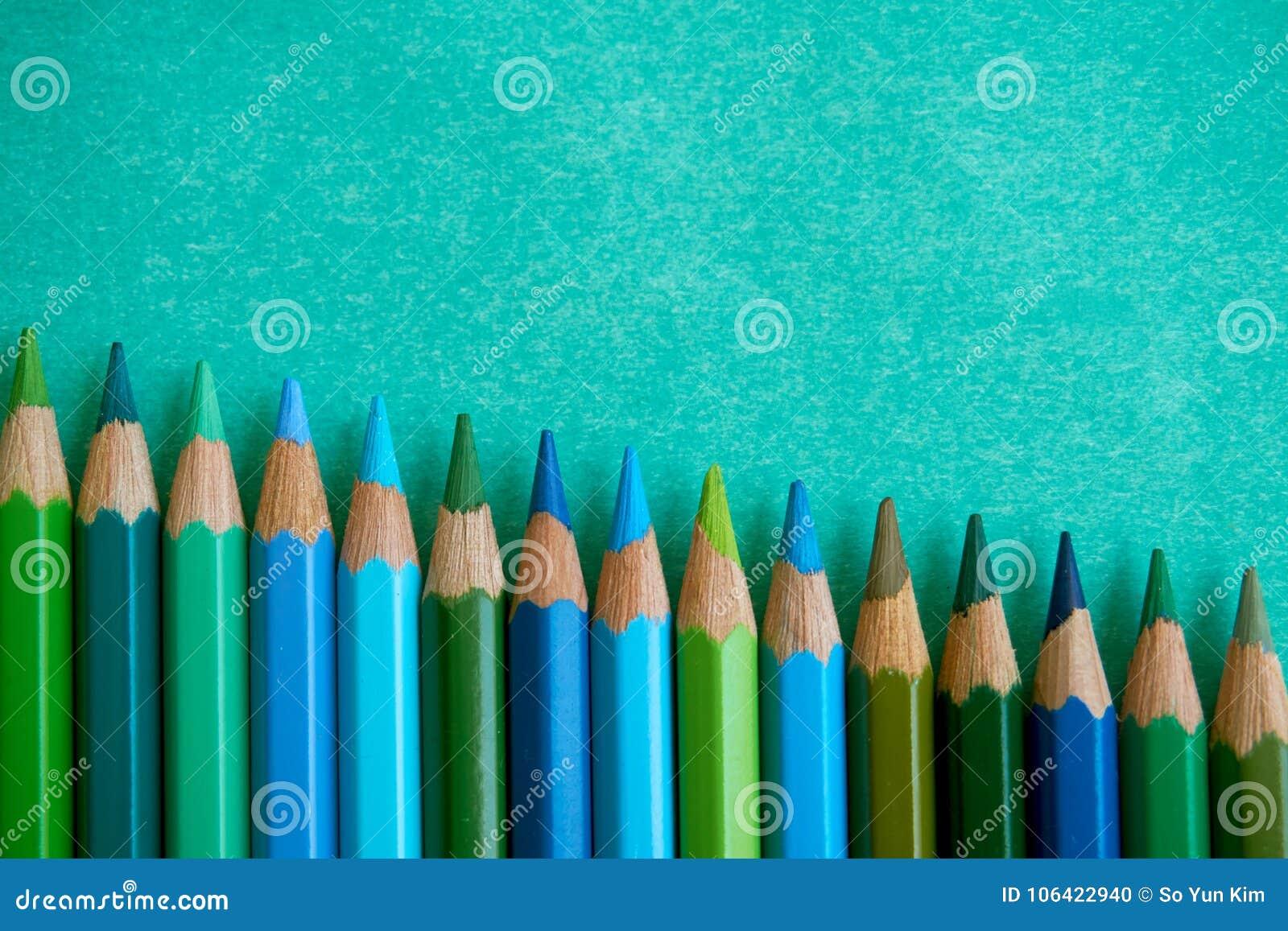 Blau und Grün färbten Bleistifte auf einem blauen Hintergrund