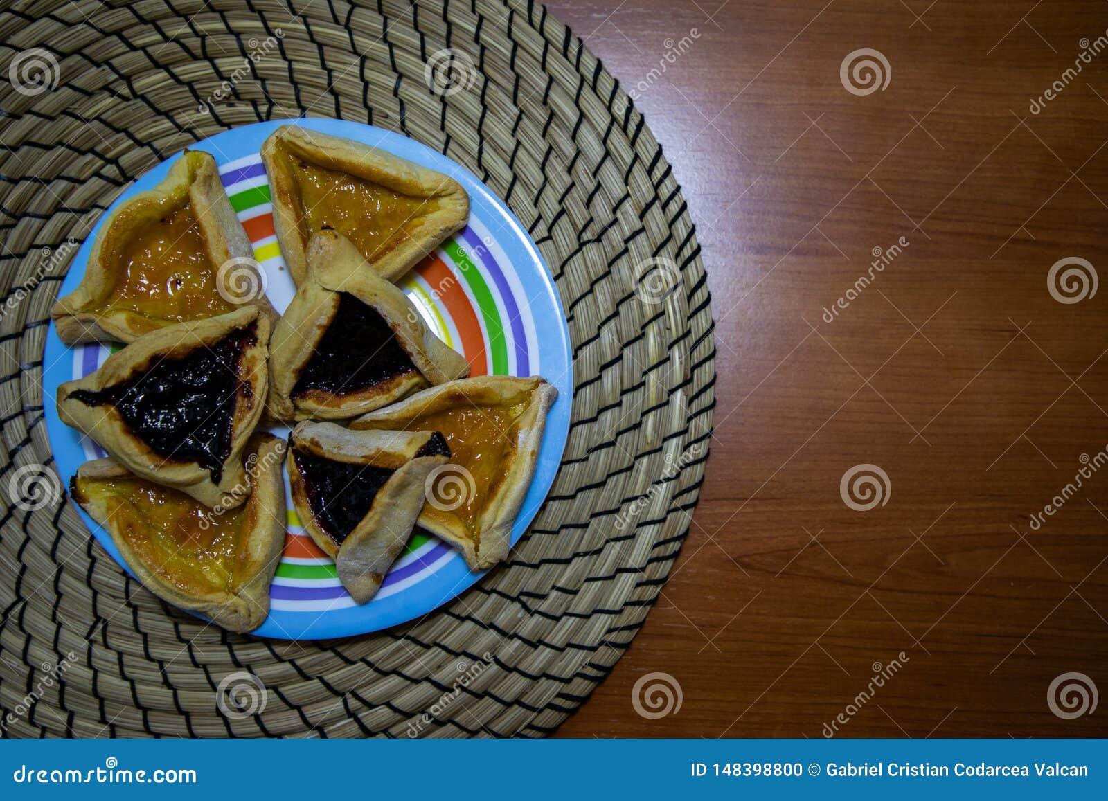 Blaubeer- und Aprikosenstaupl?tzchen Hamantash Purim in farbiger Platte mit Holztischhintergrund