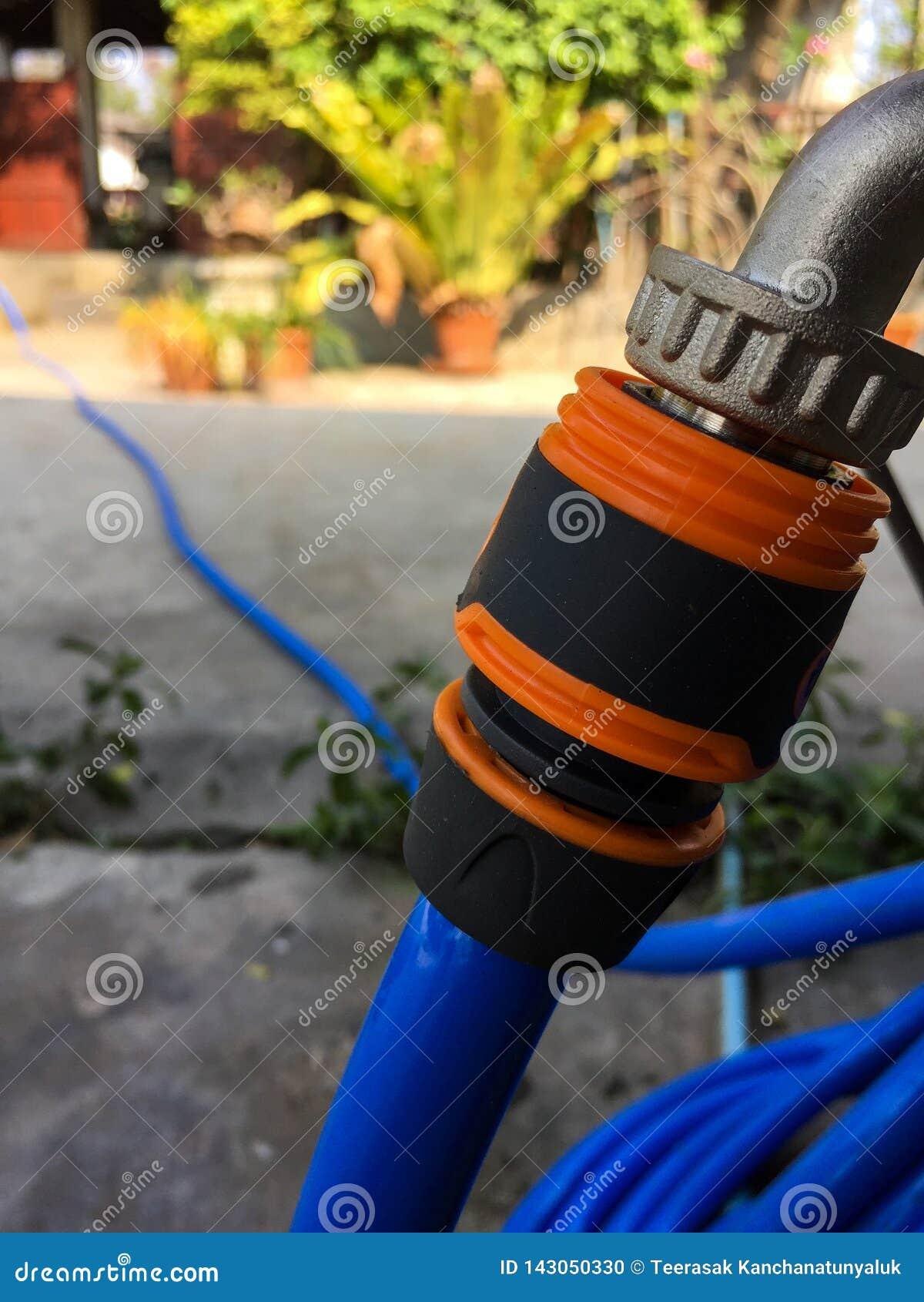 Blaue Gartenwasser-Schlauchdüse und orange Verbindungsstück
