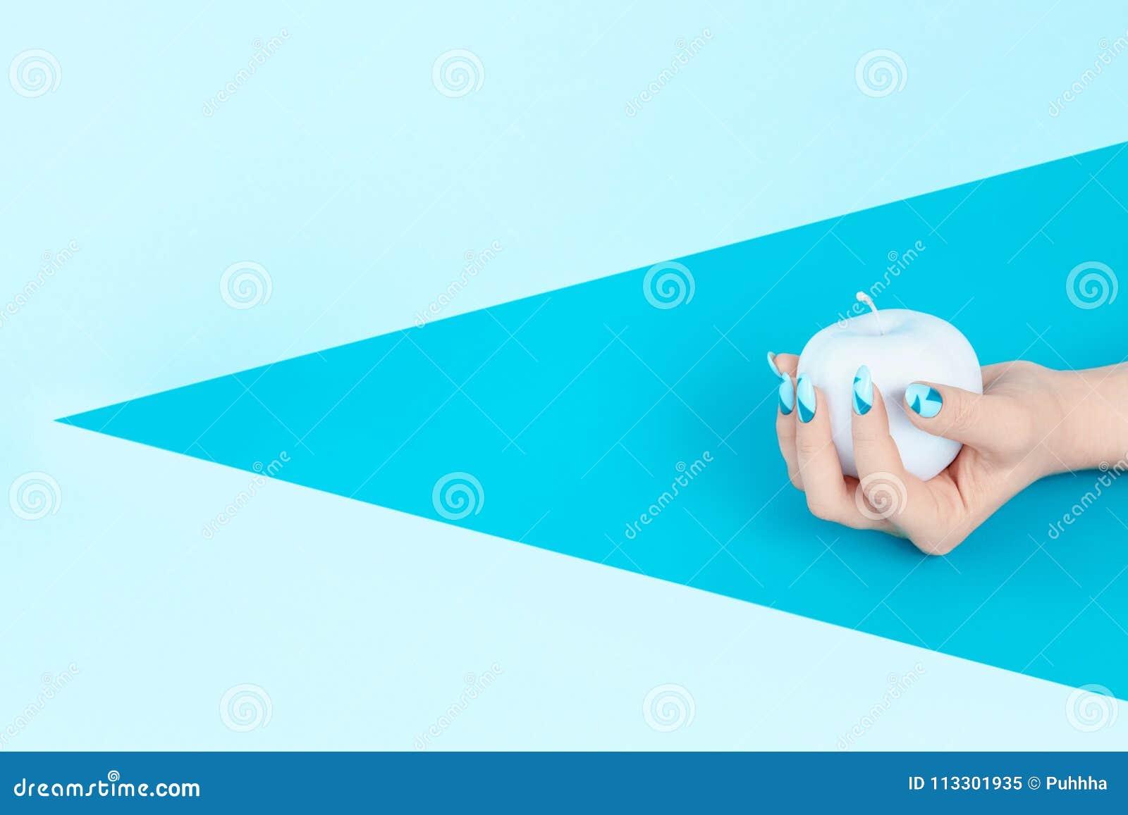 Blaue Nägel und Apple in der Hand