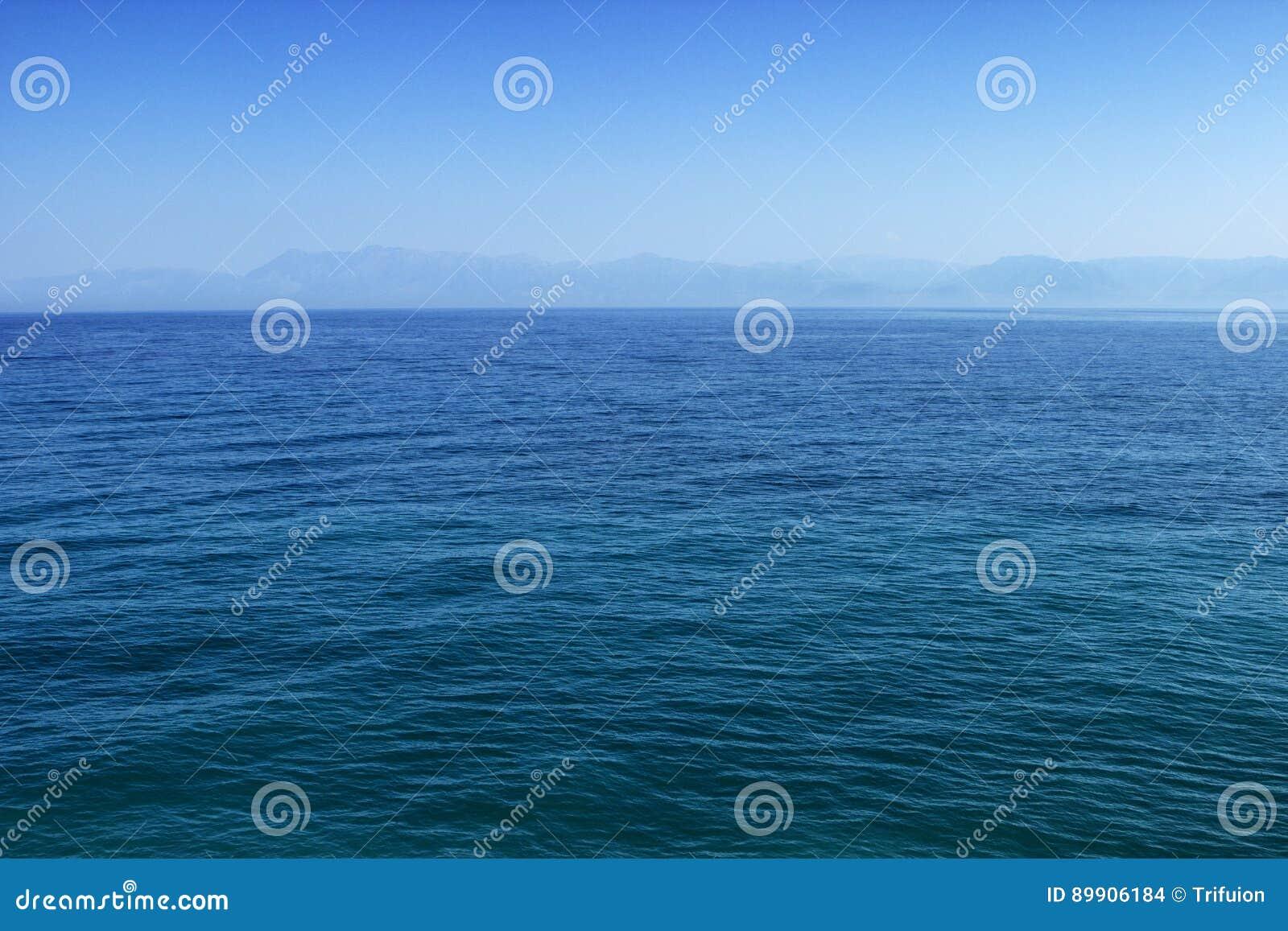 Blaue See- oder Ozeanwasseroberfläche mit Horizont und Himmel