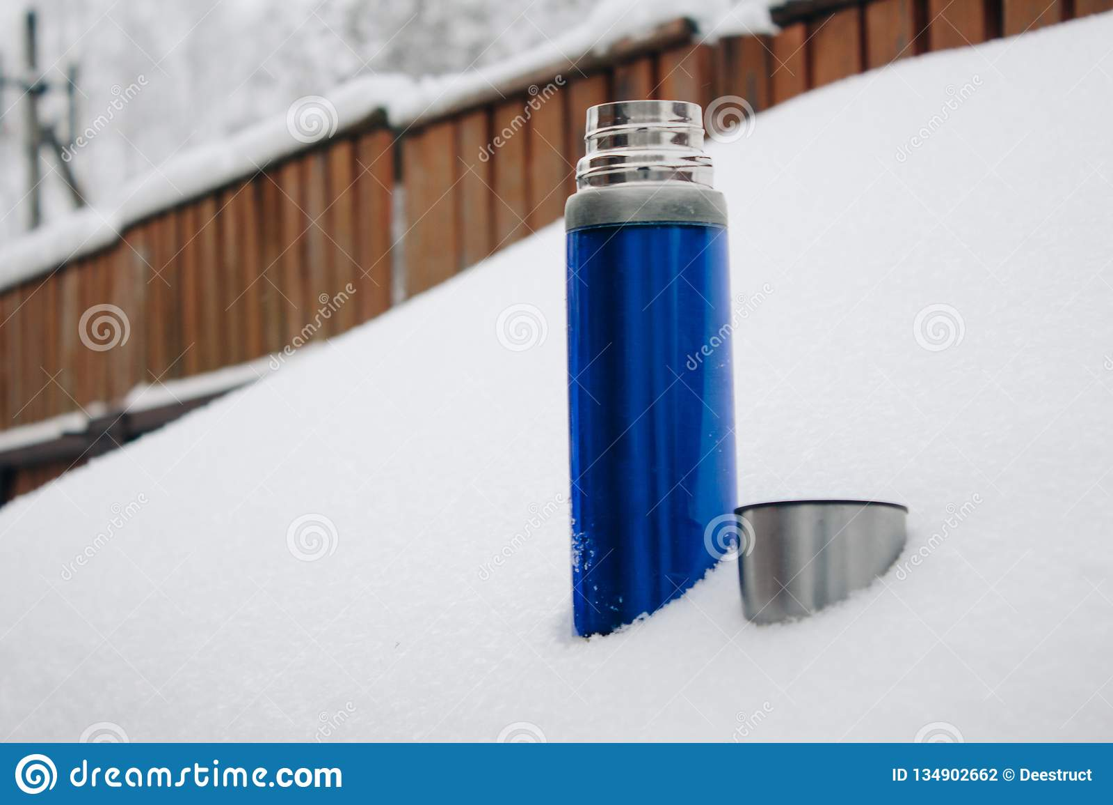 Blaue silberne Thermosflasche der Nahaufnahme mit Kaffee oder Tee im Schnee im Hinterhof Winterurlaube, heißes Getränkkonzept