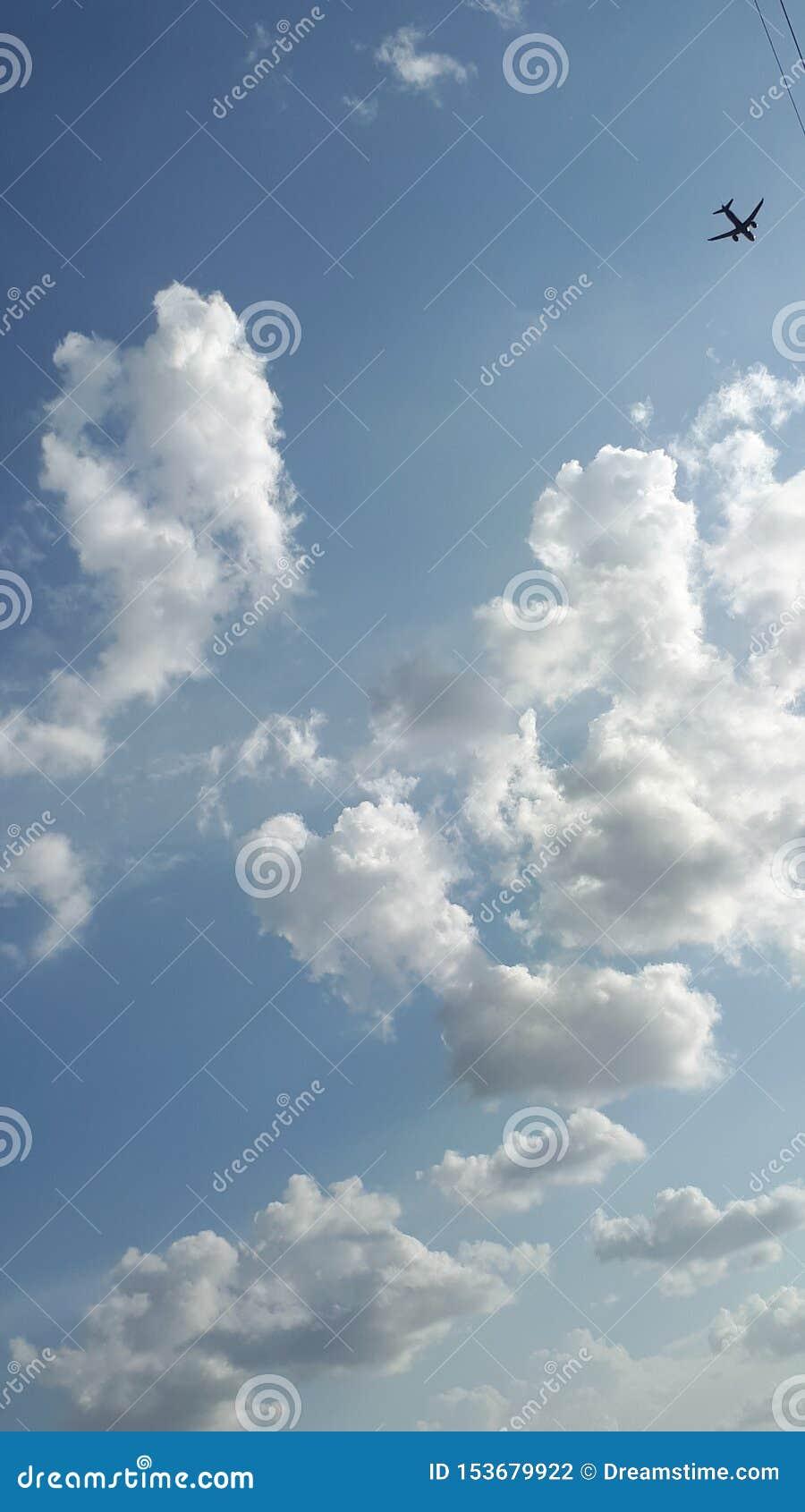 Blauer bewölkter Himmel des Sonnenscheins