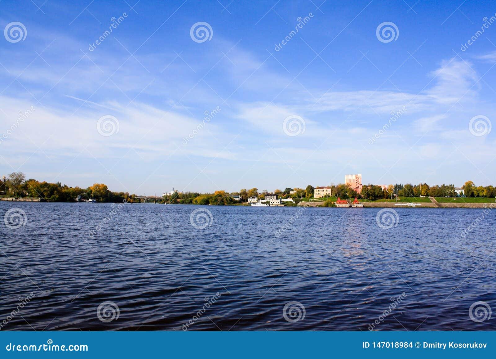 Blauer Himmel, Fluss und Stadt auf dem Ufer