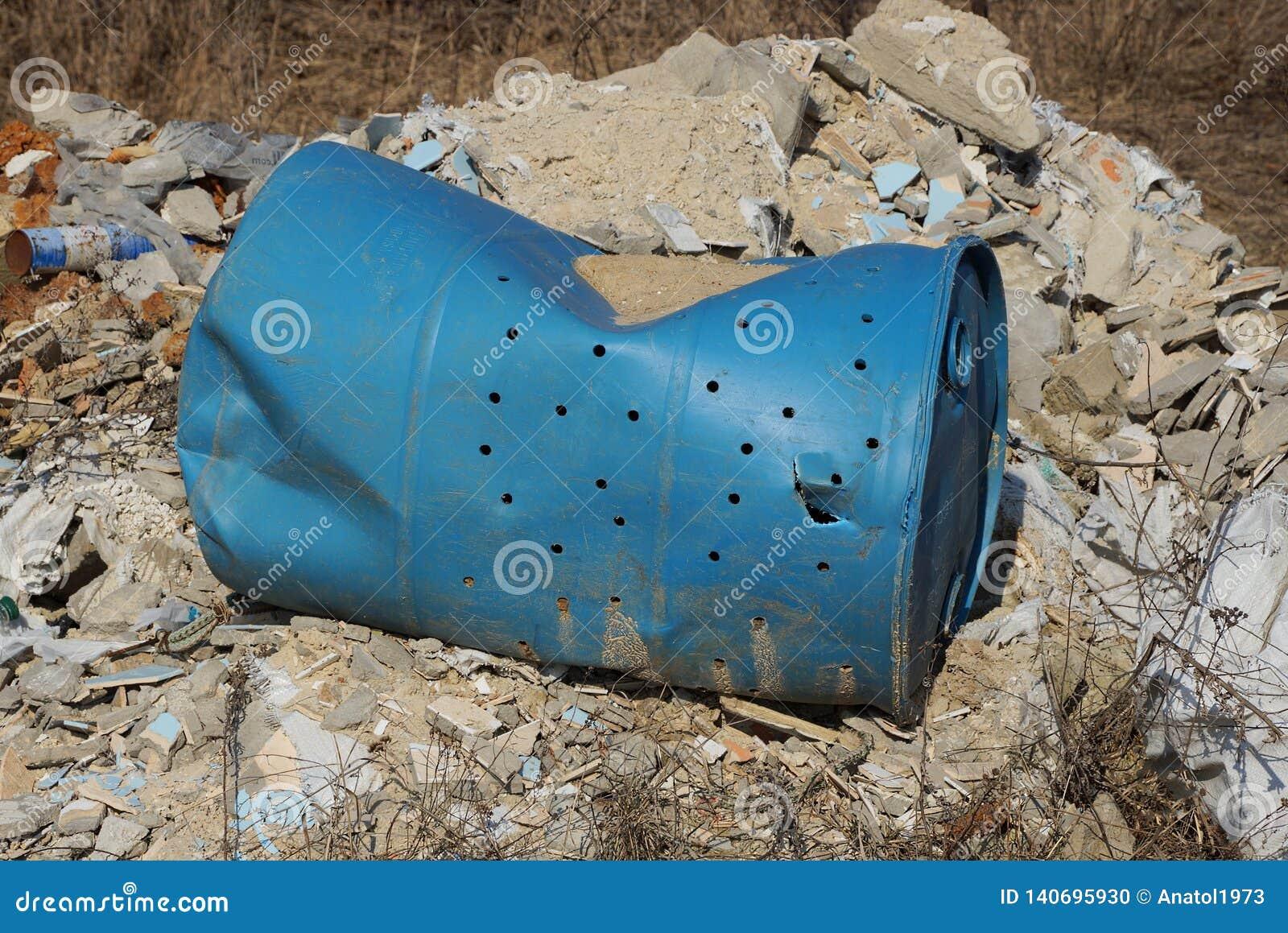 Blaues altes zerknittertes Plastikfaß liegt auf einem Stapel des Abfalls auf der Straße