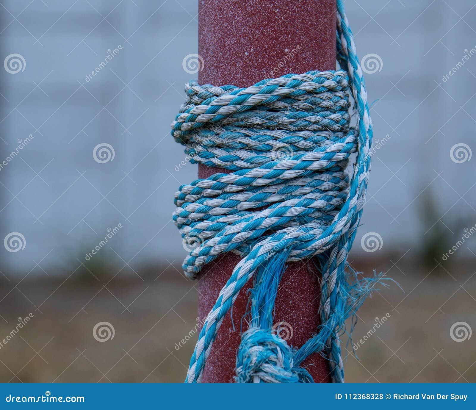 Blaues und weißes Seil knotete und Wunde um einen Pfosten