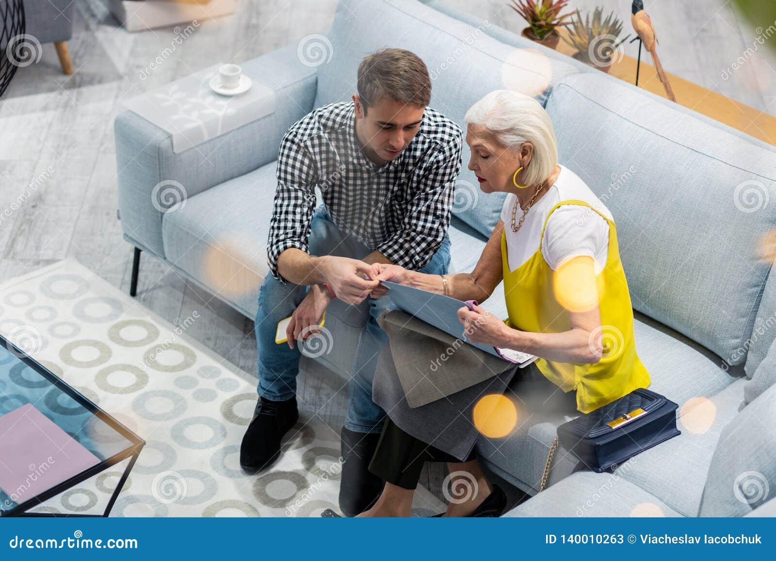 Blauw-gespoeld mevrouw die gesprek met zoon hebben die laag het textiel selecteren overeenstemmen