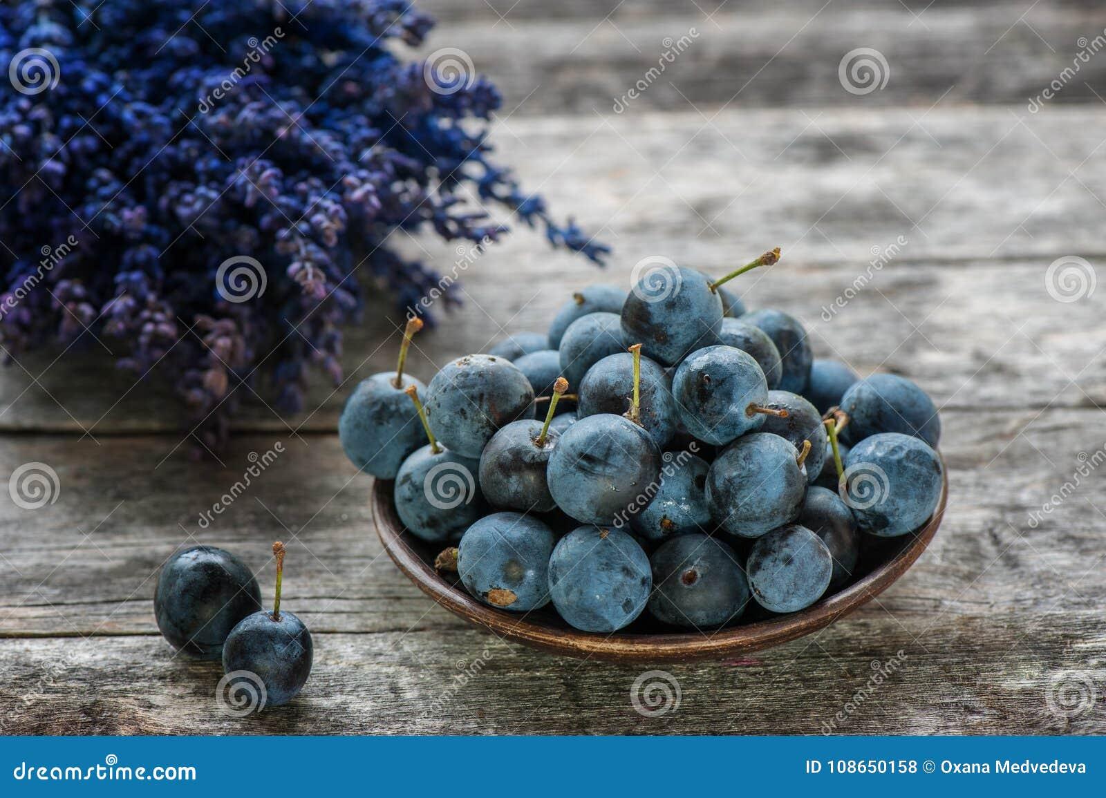 Blauwe de sleedoornbessen van de de herfstoogst op een houten lijst met een boeket van lavendel op de achtergrond De ruimte van h