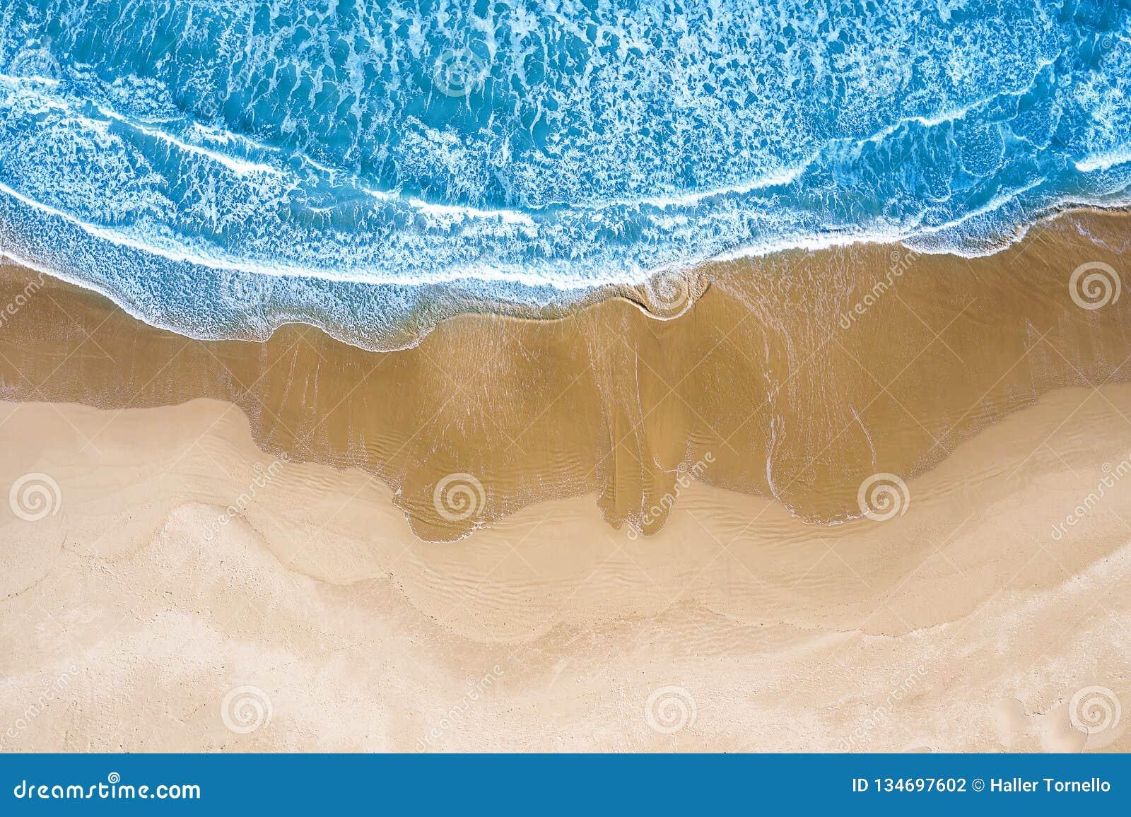 Blauwe die overzees bij het strand hierboven wordt gezien van