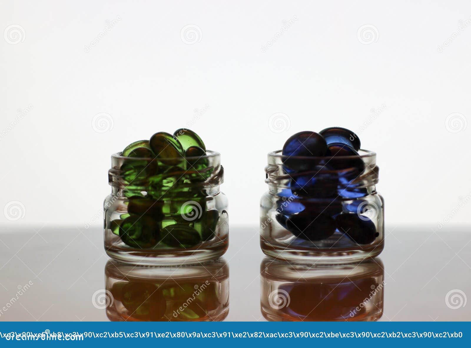 Blauwe en groene pillen in glaskruiken, korrels