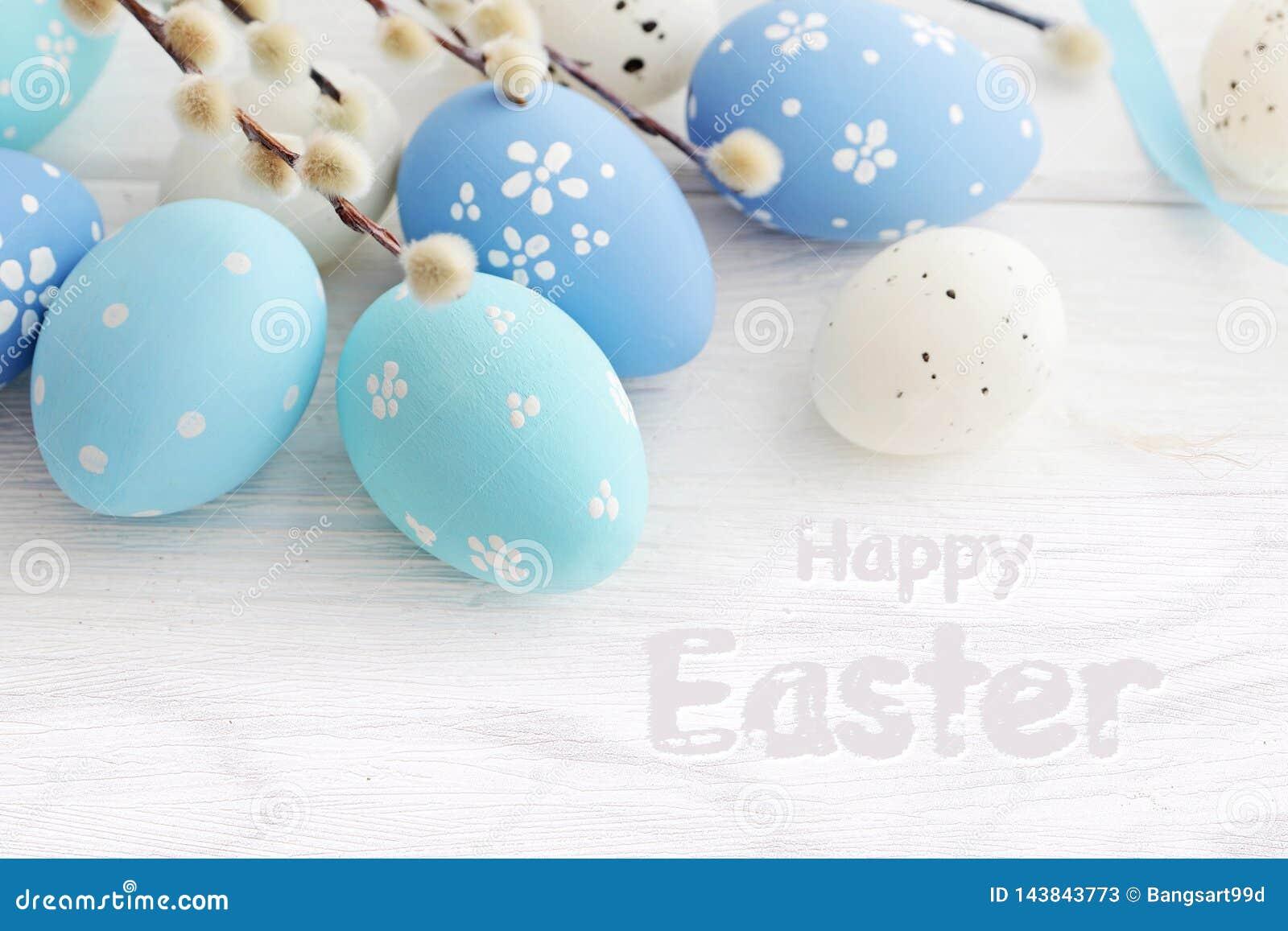Blauwe gekleurde paaseieren op de witte houten achtergrond