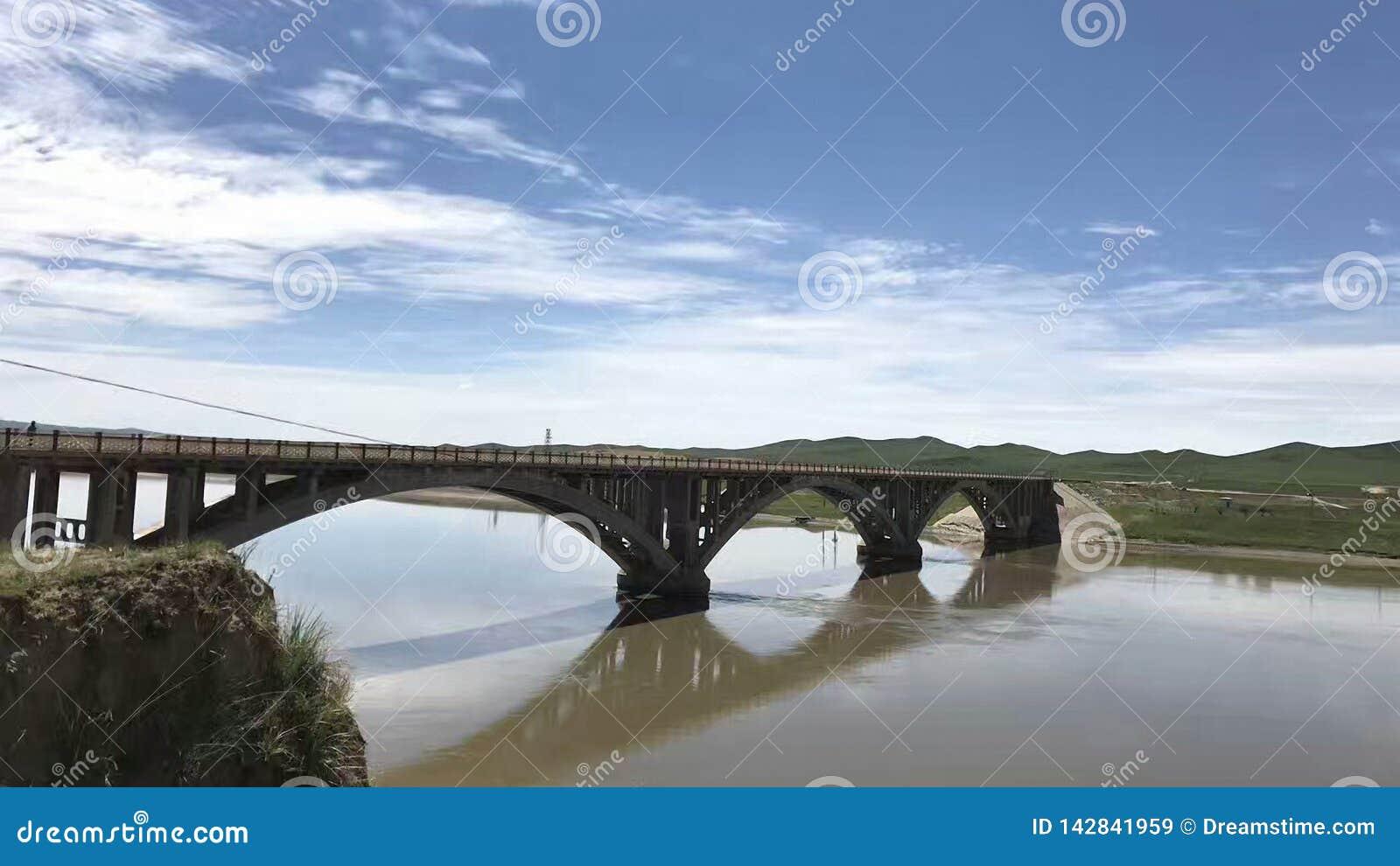 Blauwe hemel en witte wolken, een kleine brug over een kleine rivier