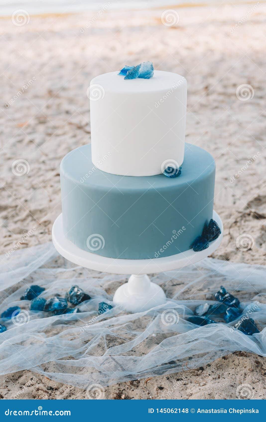Blauwe huwelijkscake op twee niveaus met op een strand