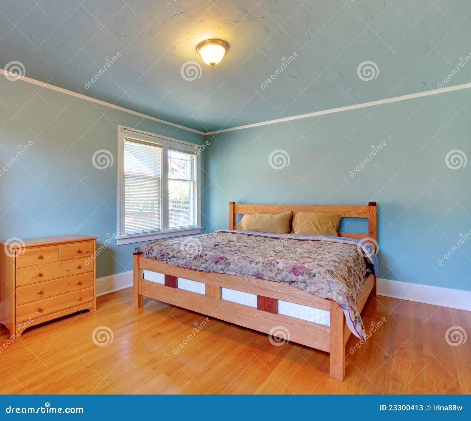 Blauwe slaapkamer met eiken vloer en groot bed stock foto for Slaapkamer bed