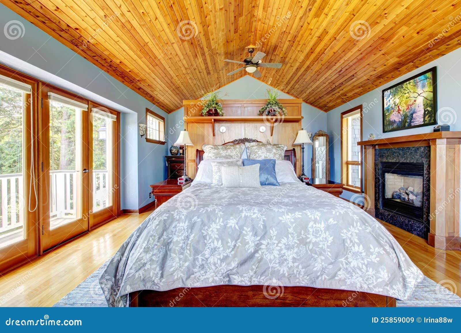 Blauwe slaapkamer met houten plafond en open haard royalty vrije ...