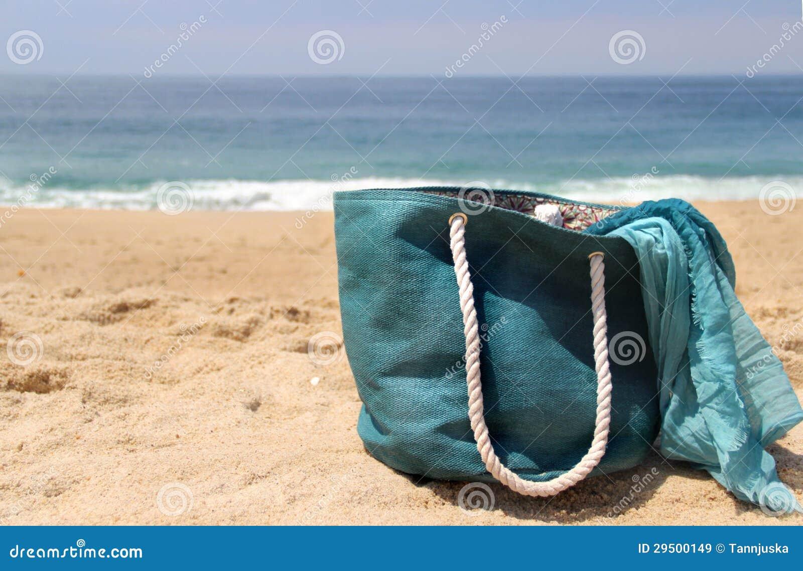 Blauwe strandzak op de zeekust en de sjaal