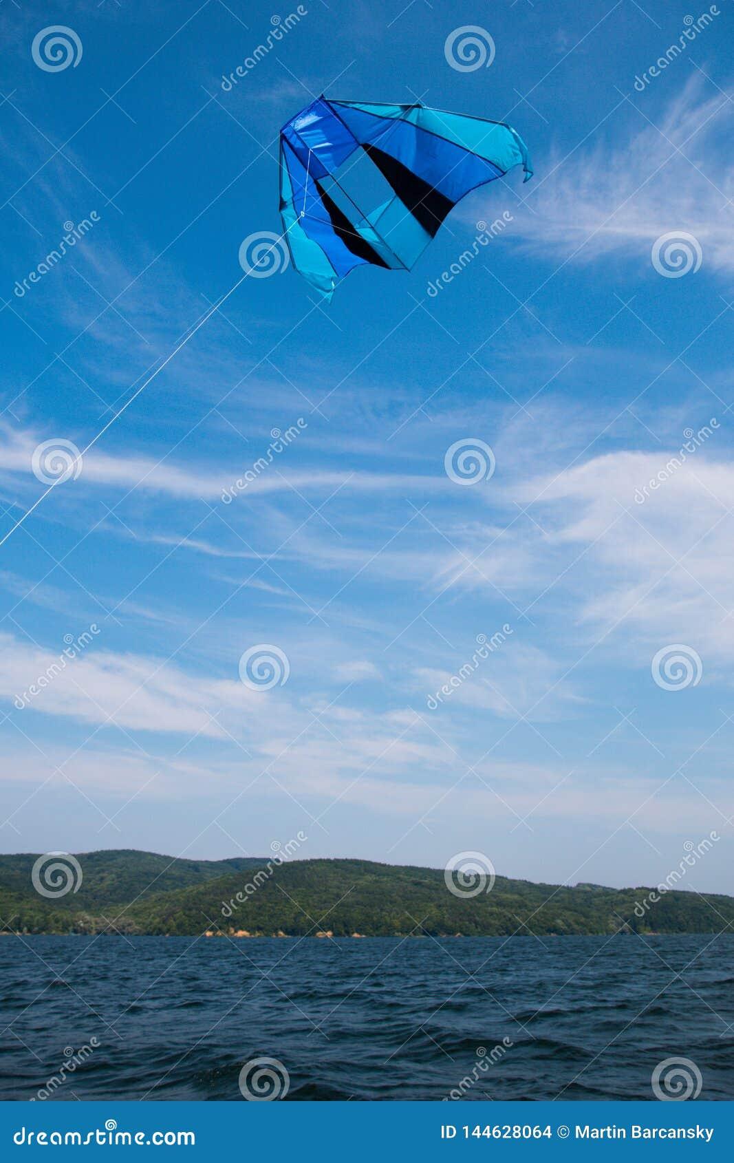 Blauwe vlieger op blauwe hemel over water