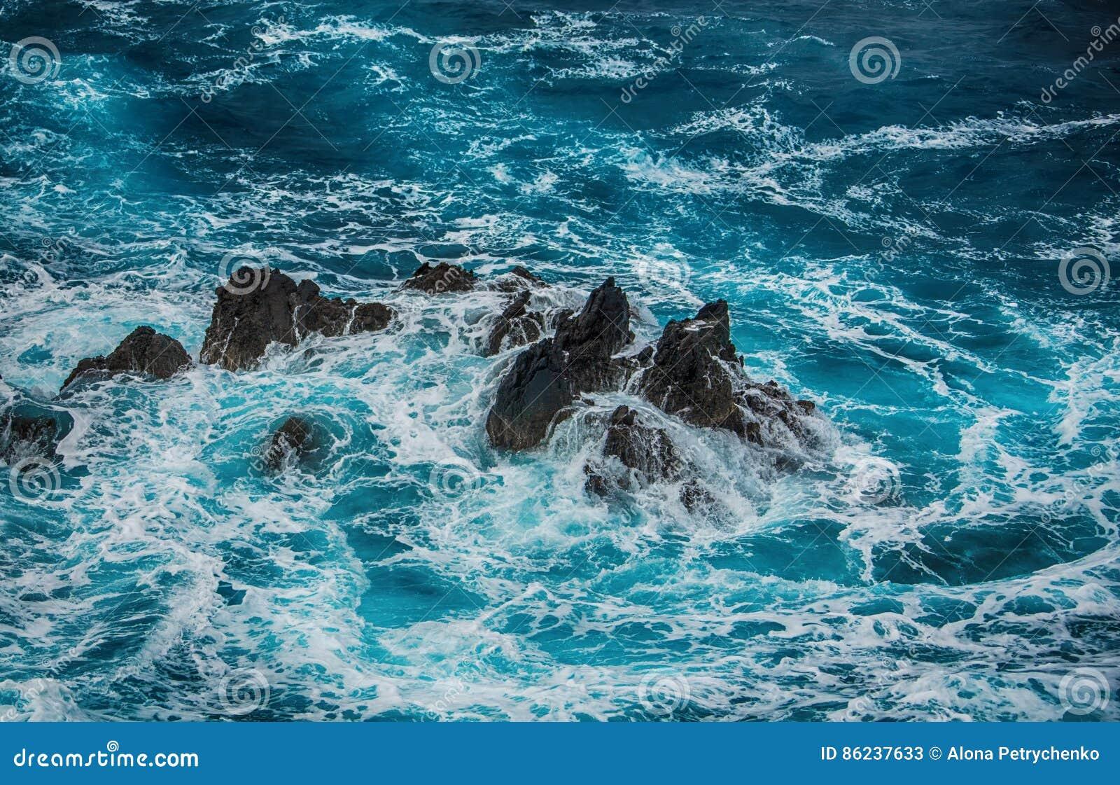 Blauwe woedende golven die op de rotsen verpletteren
