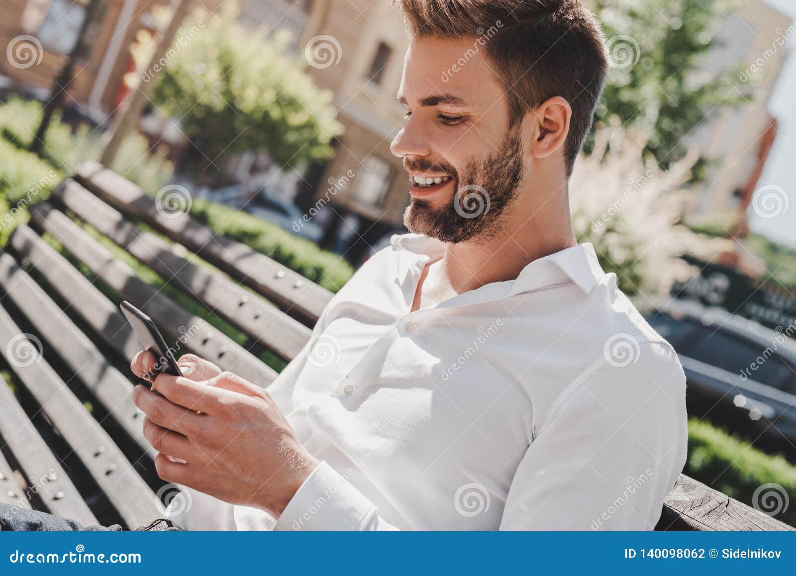Bleiben Sie in Kontakt Junger Mann, der im Park sitzt und sein Telefon betrachtet Konzept des Erfolgs