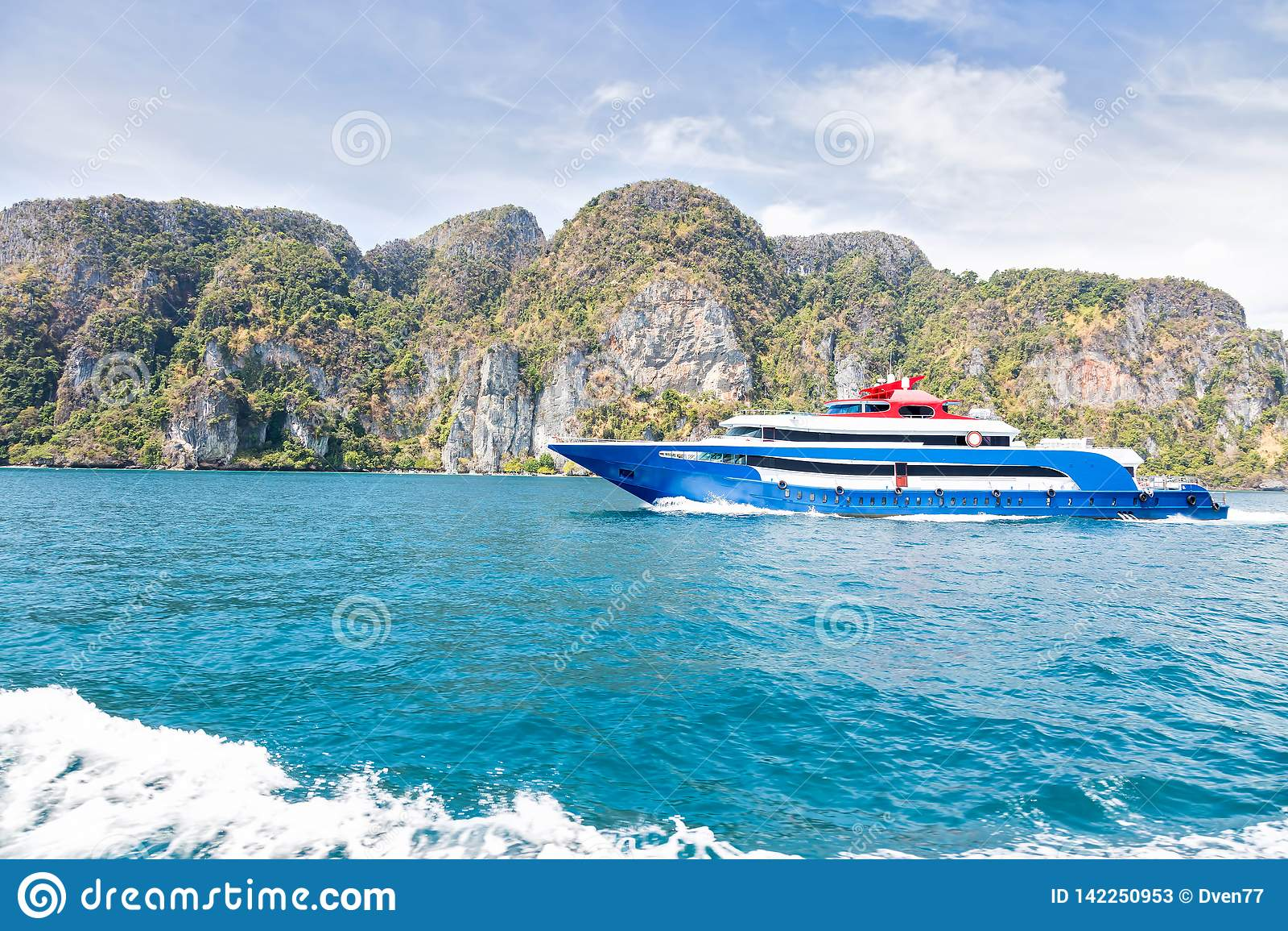 Bleu avec le bateau blanc et rouge de vitesse de plaisir d accents Navigation sur la mer contre une île tropicale de montagne Vue