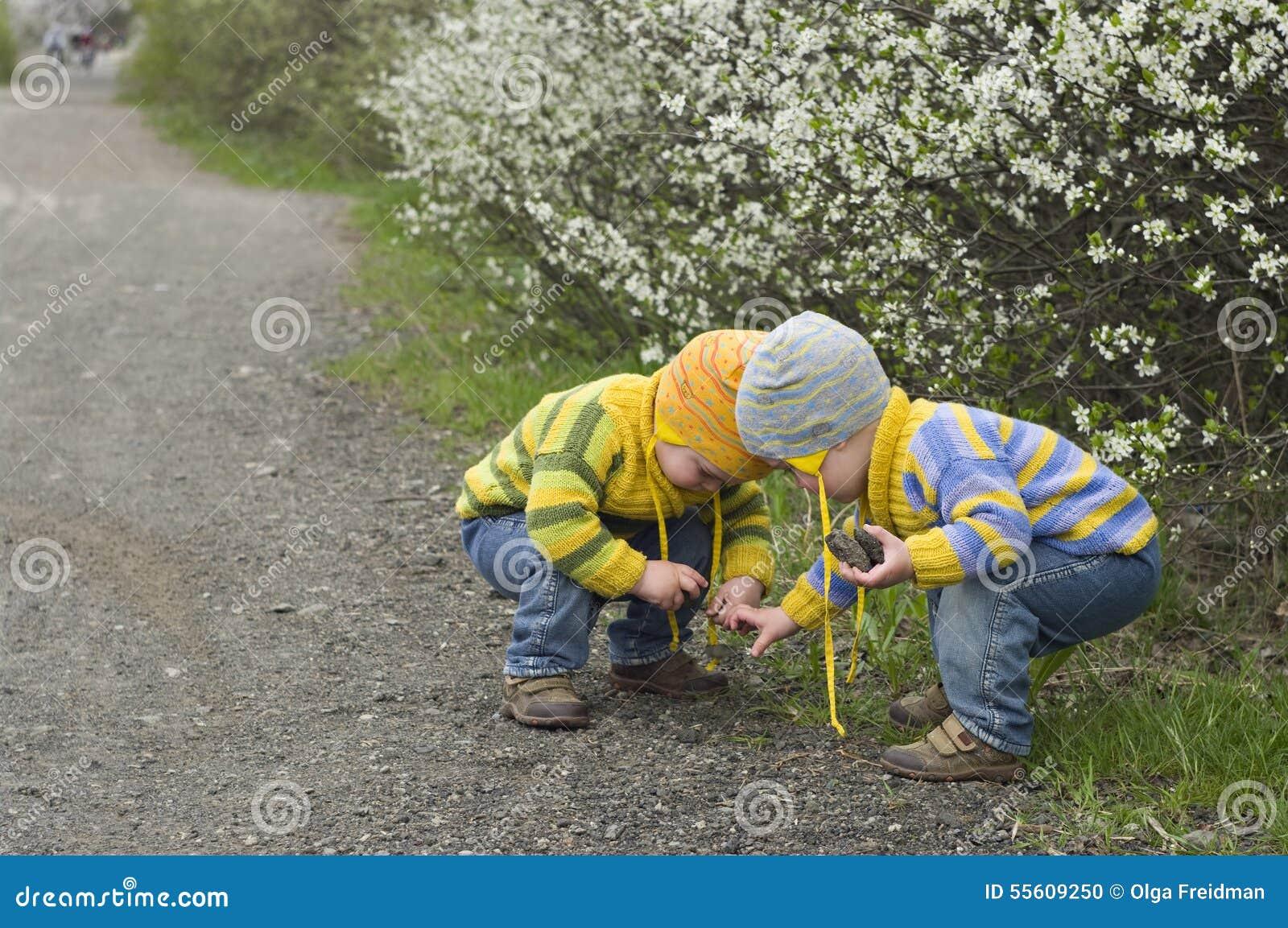 Bliźniacy kucający bawić się z kamieniami