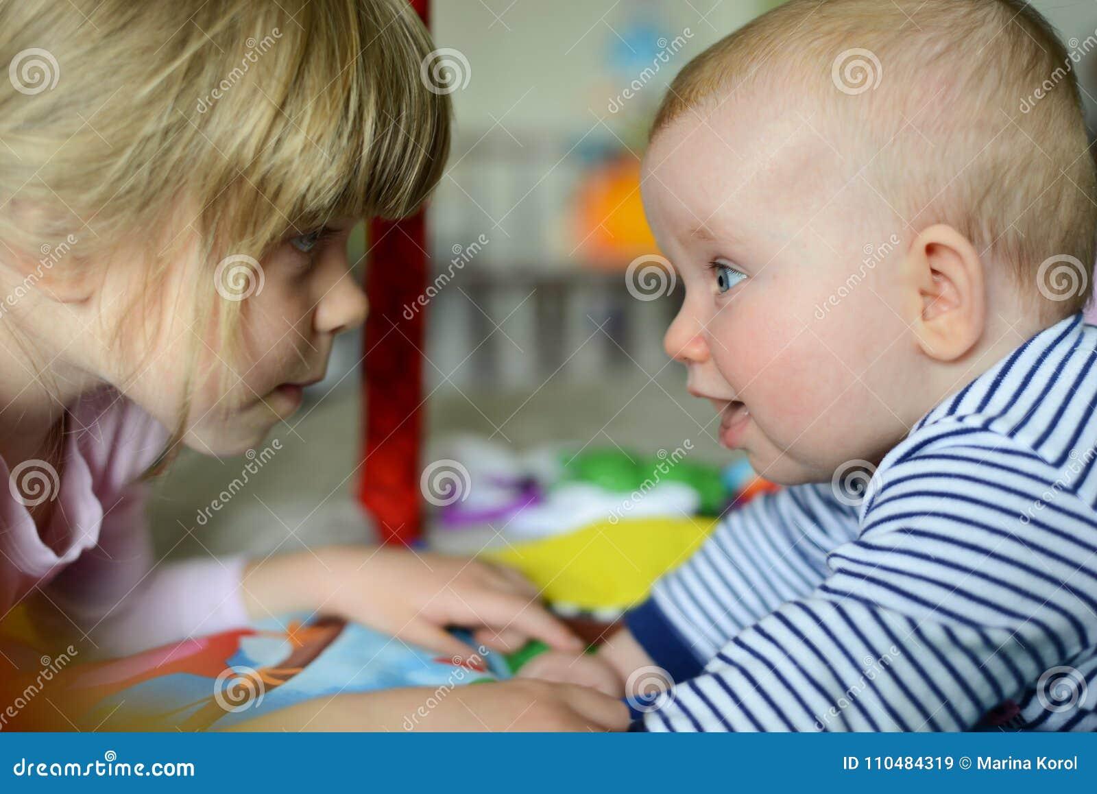 Blick för två liten förtjusande Caucasian systrar på de De är lyckliga och att le