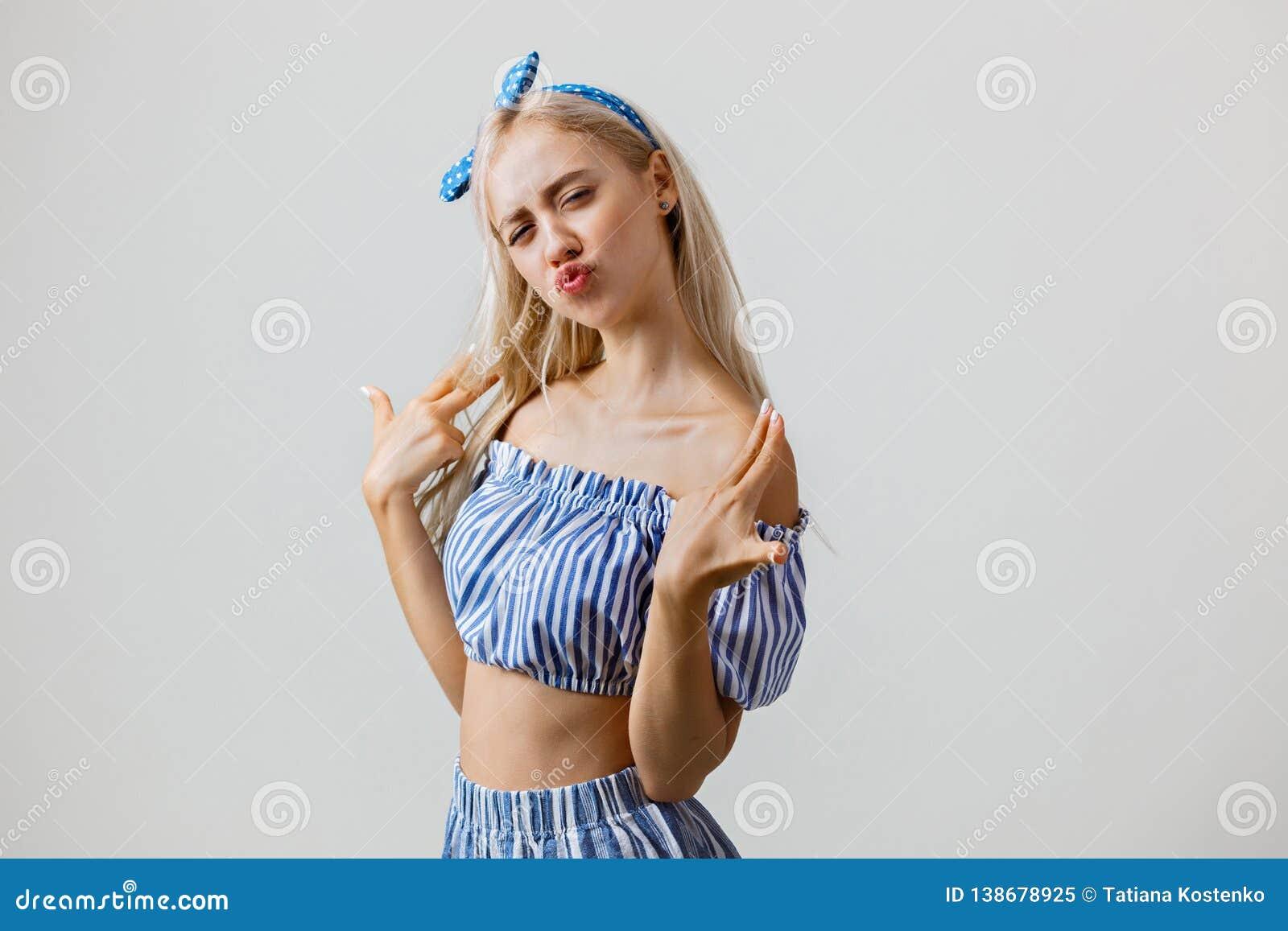 Blij en opgewekt mooi blondemeisje in de zomeruitrusting, die bij camera stellen die gebaar van het vingerkanon, maken die zich o
