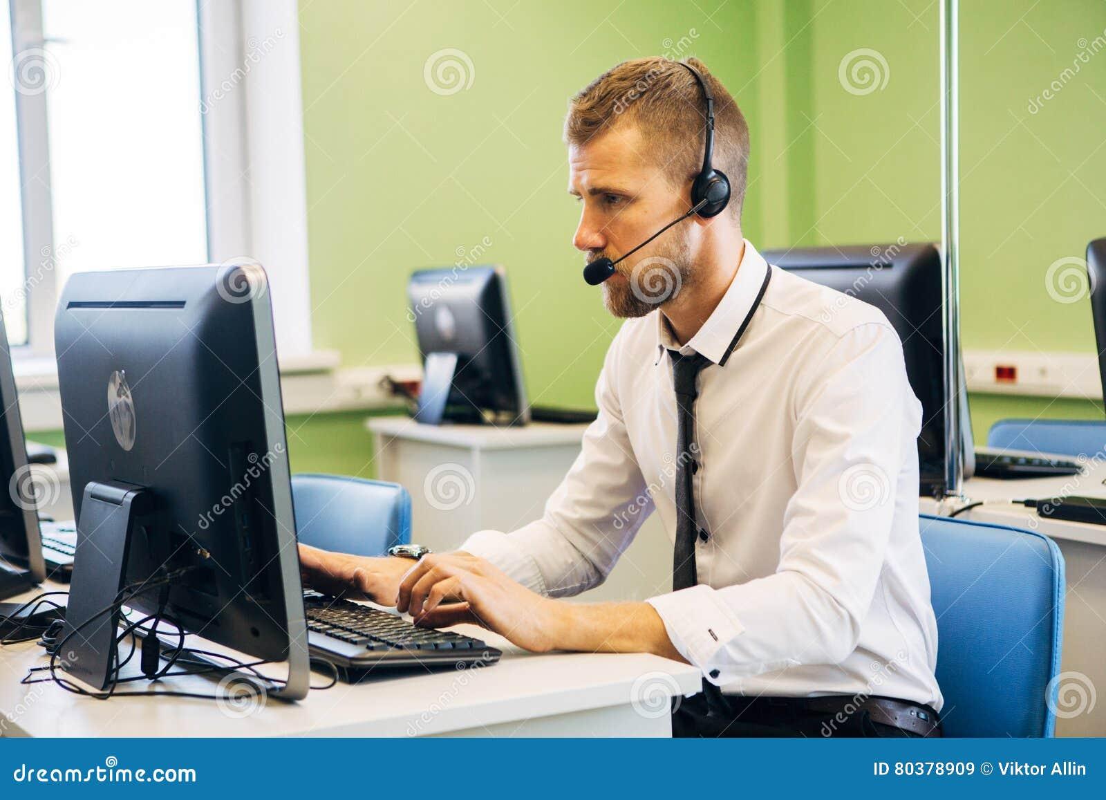 Blije agent die in een call centre met zijn hoofdtelefoon werken