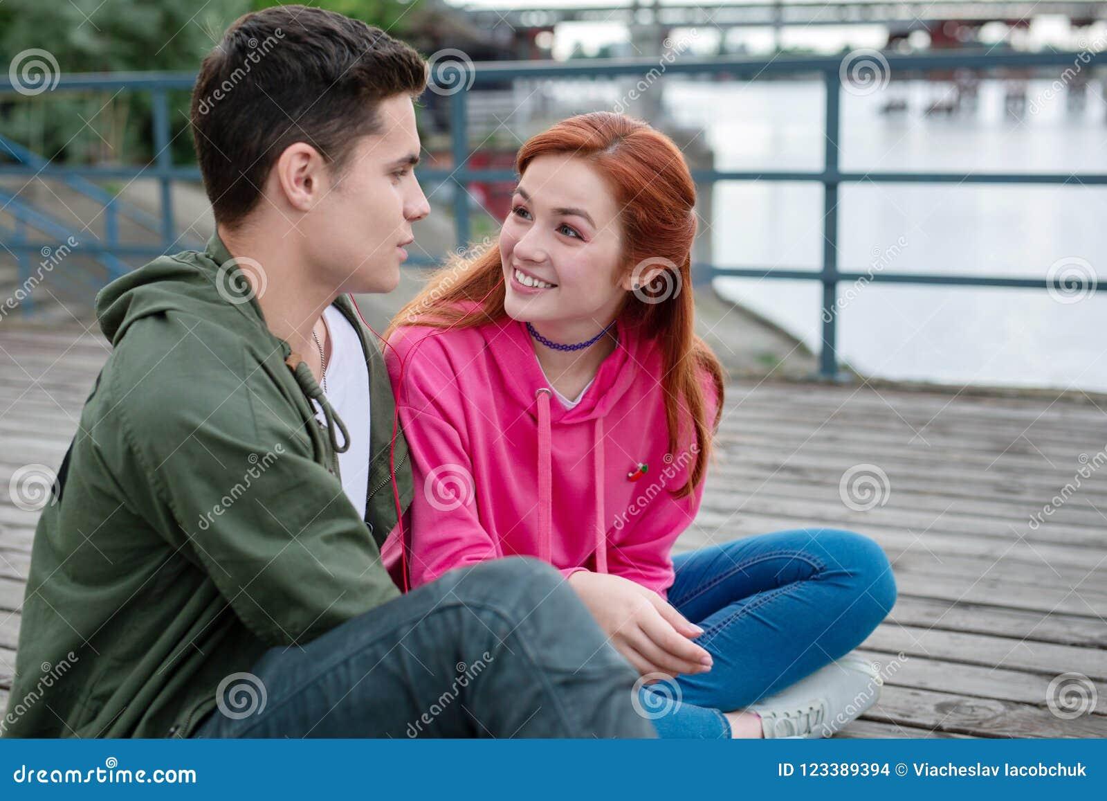 Blije jonge vrouw die haar vriend bekijken