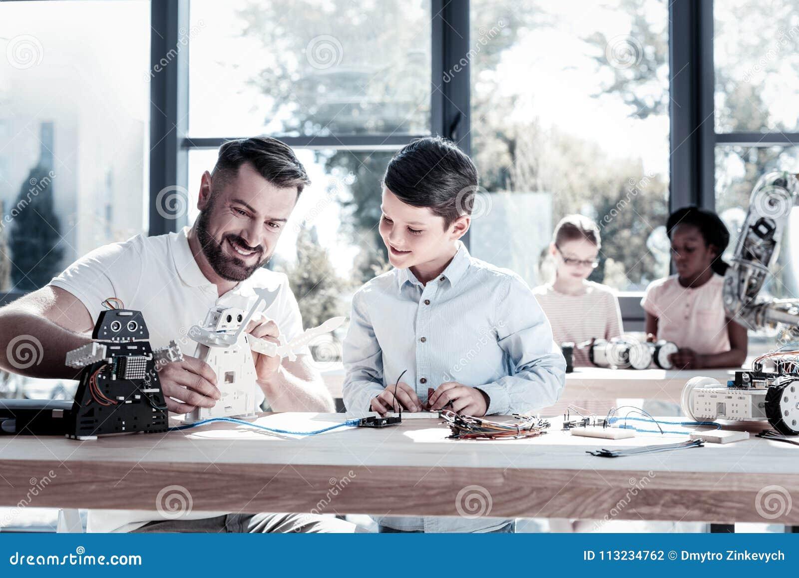 Blije leraar en student die terwijl het werken aan robotachtige machine glimlachen
